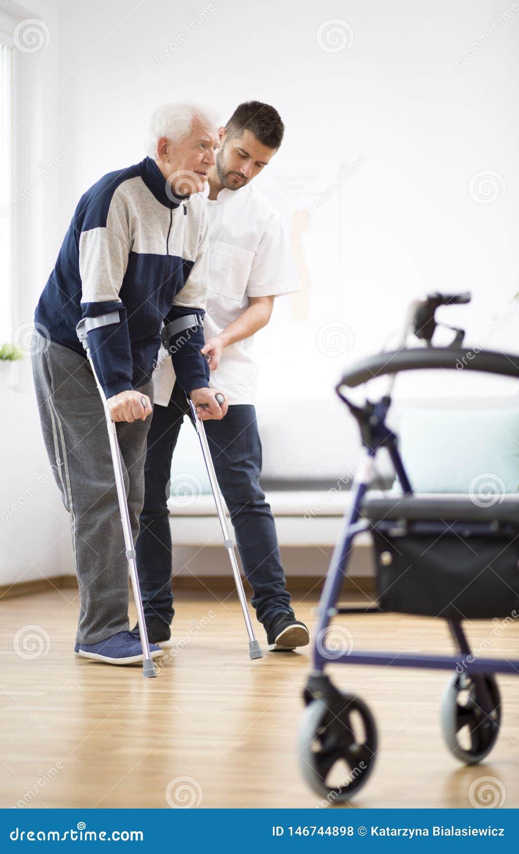 年长人走在拐杖的和支持他的一位男性护士