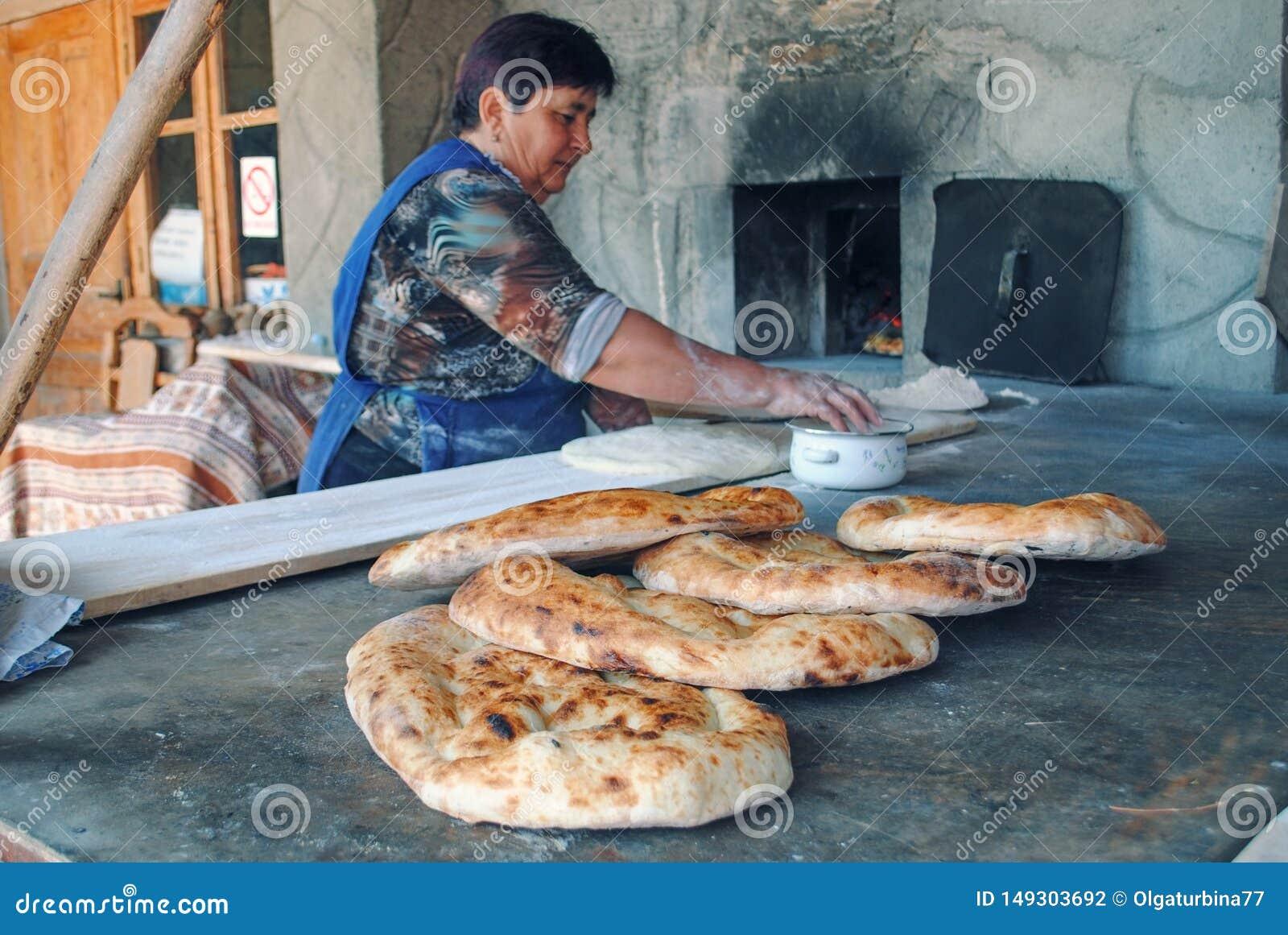 年长在烤箱的妇女烘烤的面包