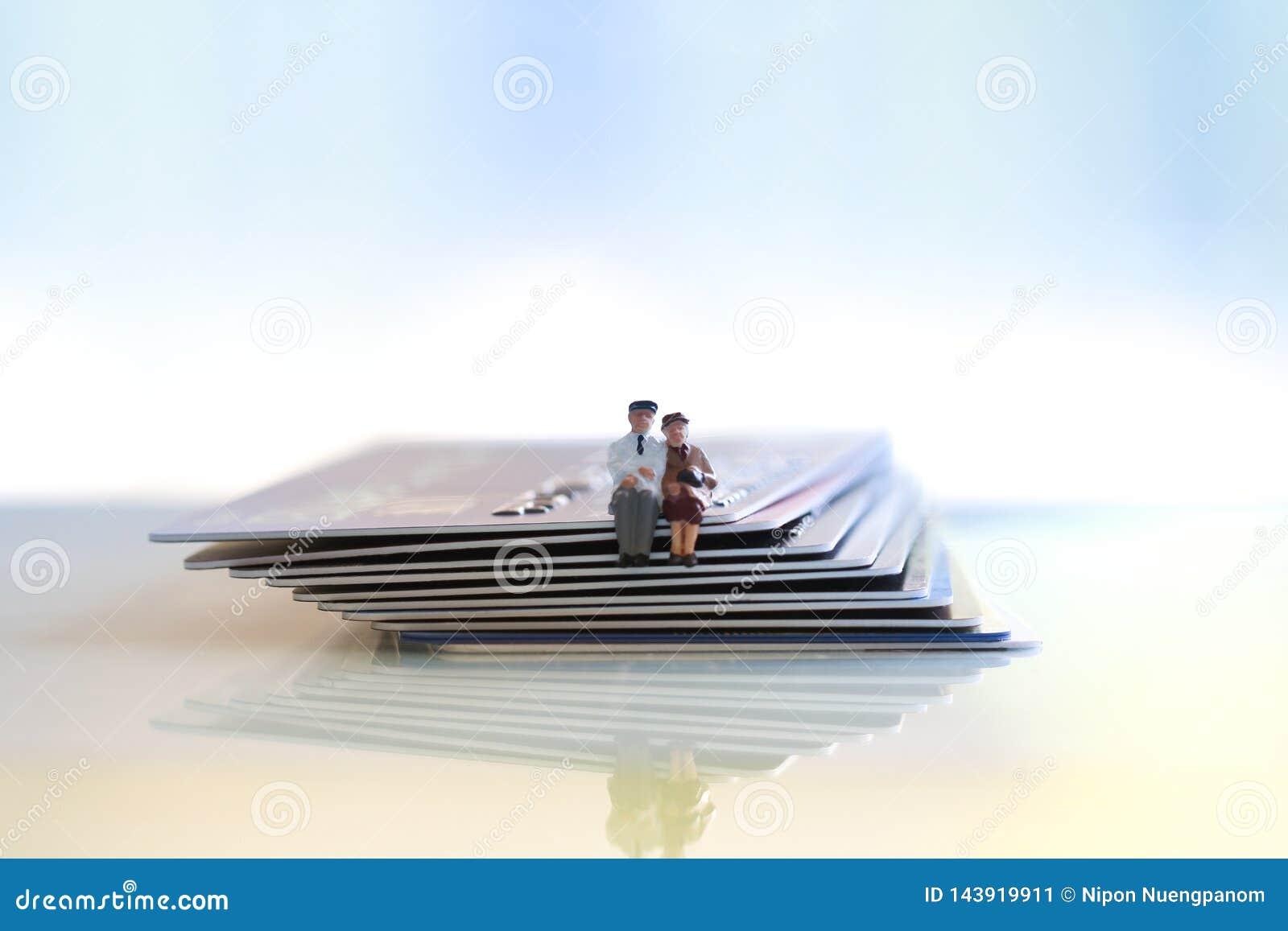 年长夫妇坐信用和借记卡在木桌上