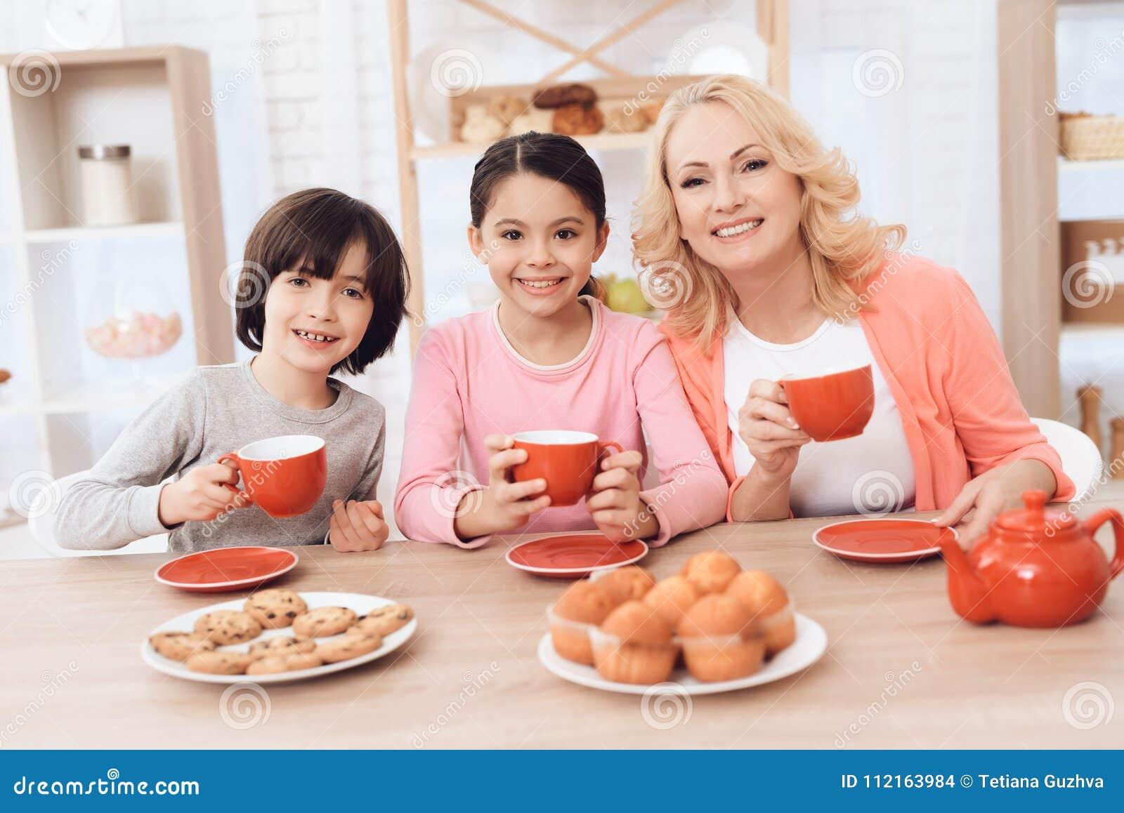 年长妇女和快乐的孙子和孙女在厨房里喝从红色杯子的茶