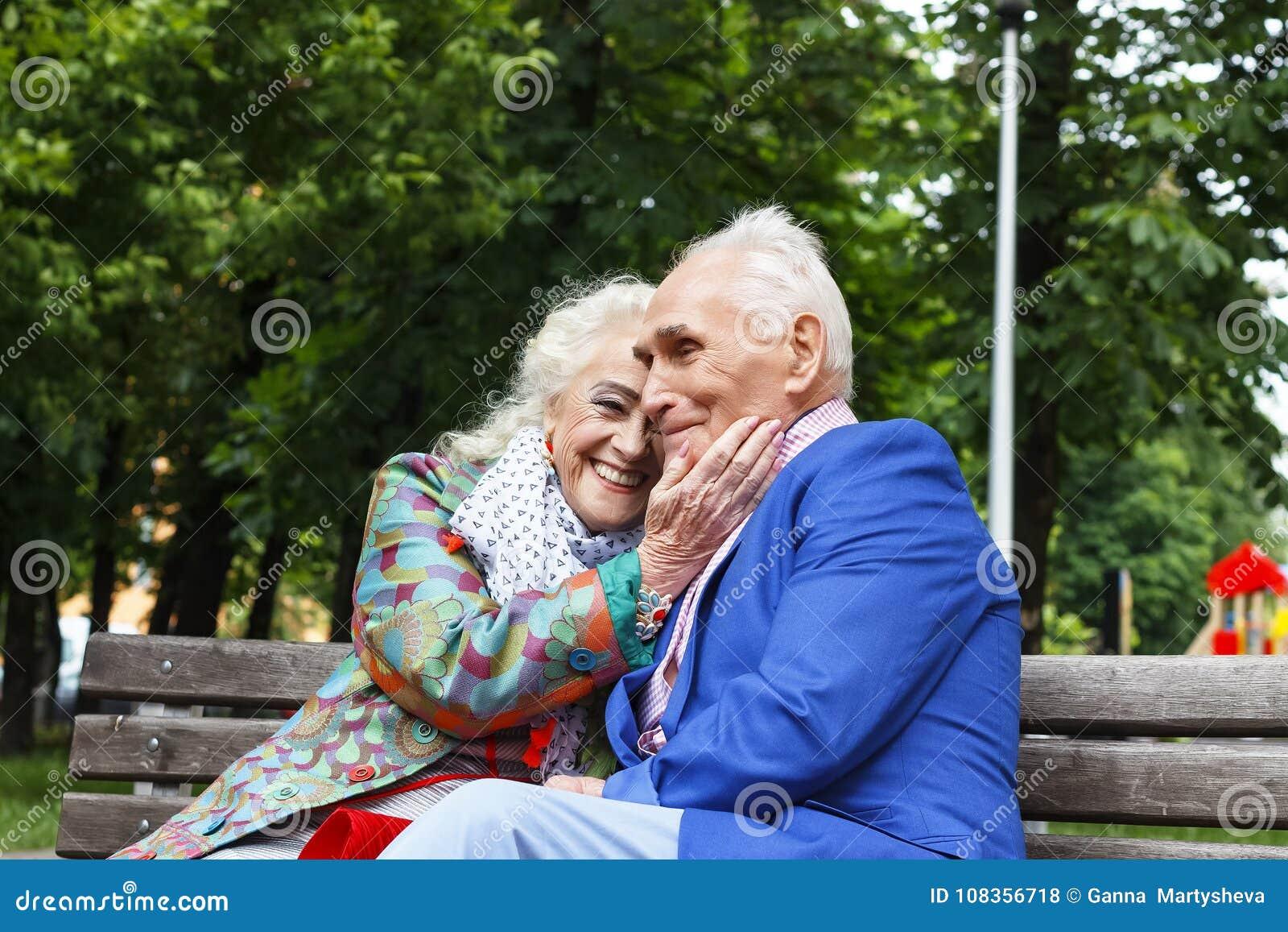 年长家庭夫妇谈话在一条长凳在城市停放 愉快前辈约会