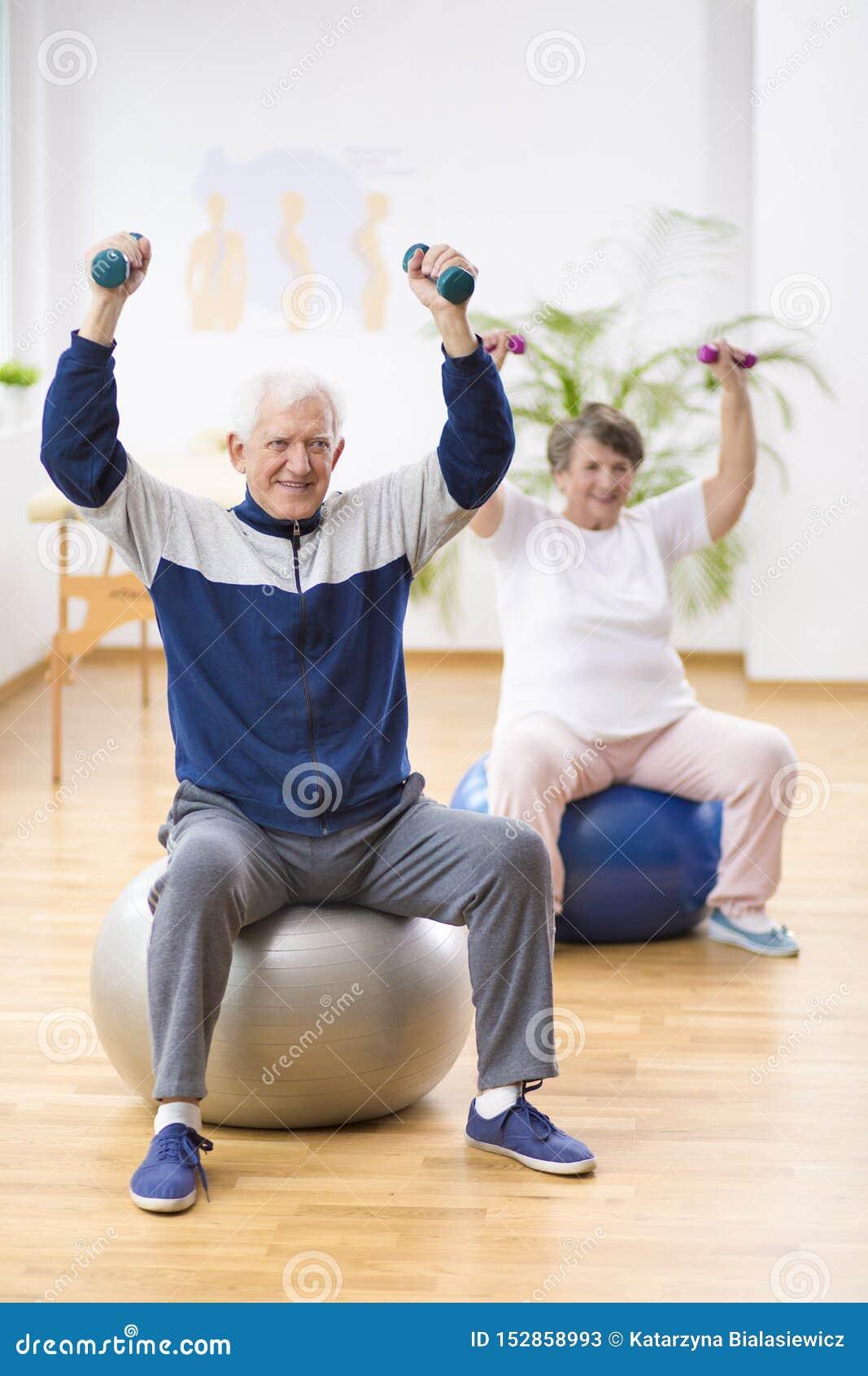 年长行使在体操球的男人和妇女在物理疗法会议期间在医院