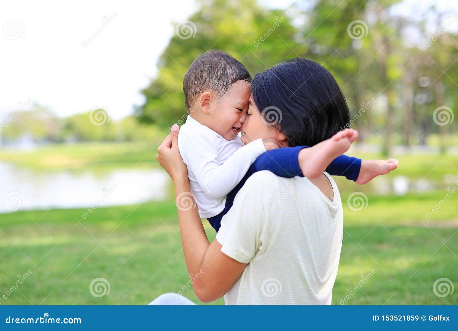 幸福家庭亚裔使用在自然庭院里的妈妈和她的儿子 母亲运载的儿子