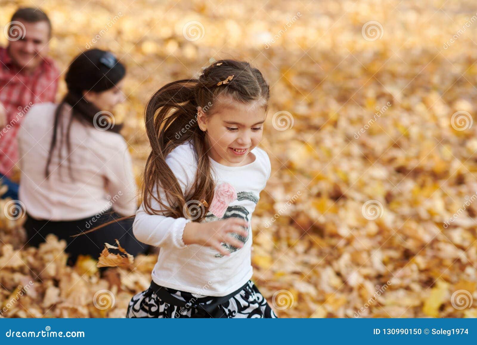 幸福家庭在秋天城市公园 子项和父项 他们摆在,微笑,演奏和获得乐趣 明亮的黄色树