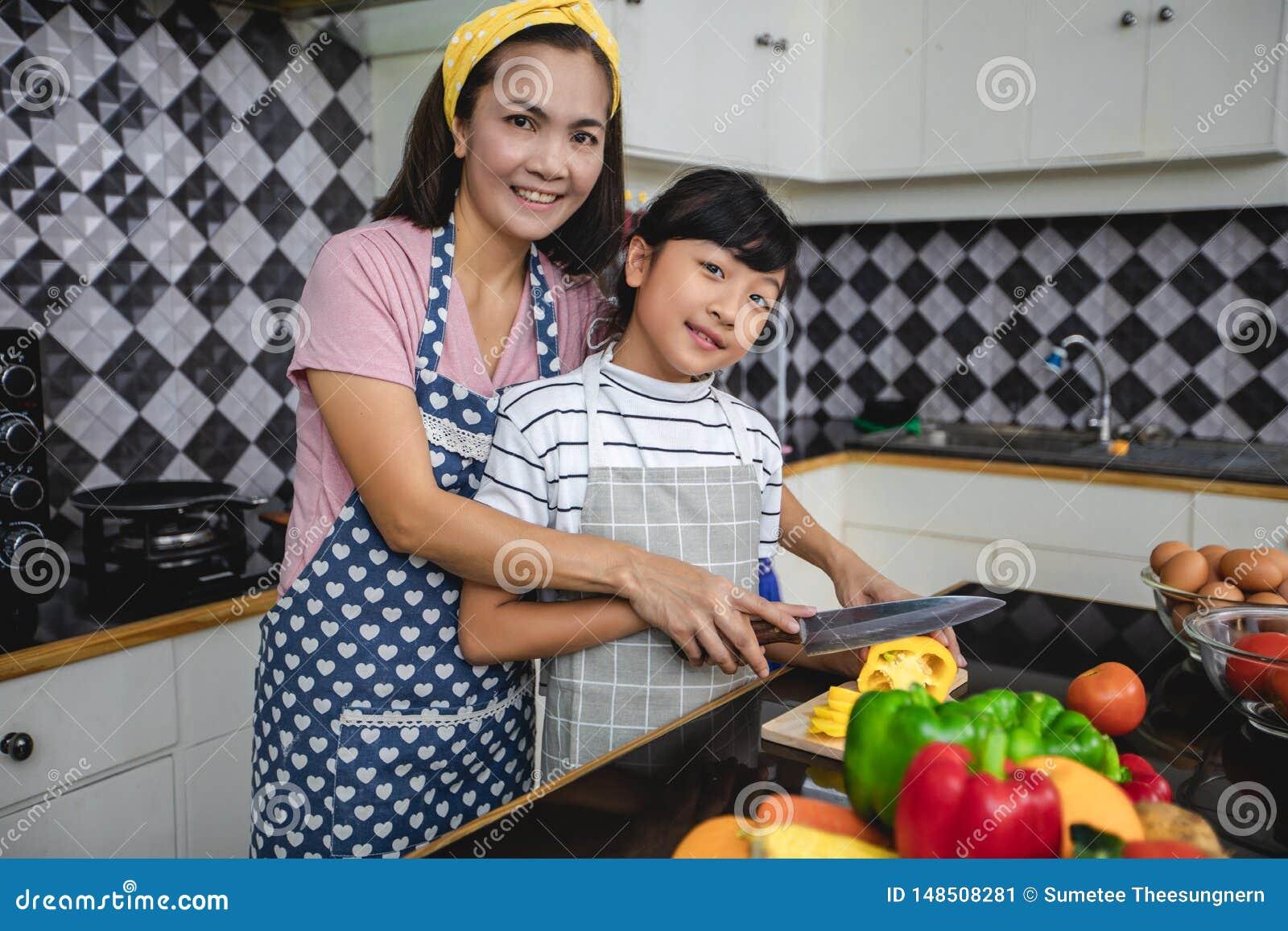 幸福家庭有爸爸、的妈妈和一起烹调他们的小的女儿在厨房