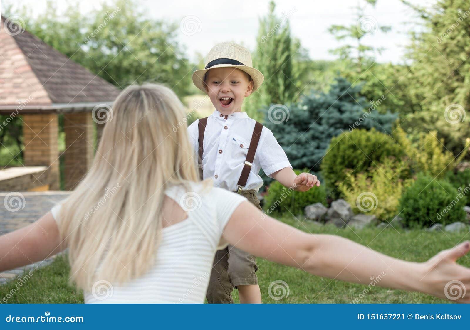 幸福家庭的生活片刻!一起使用母亲和儿子的孩子获得乐趣在草在晴朗的夏日