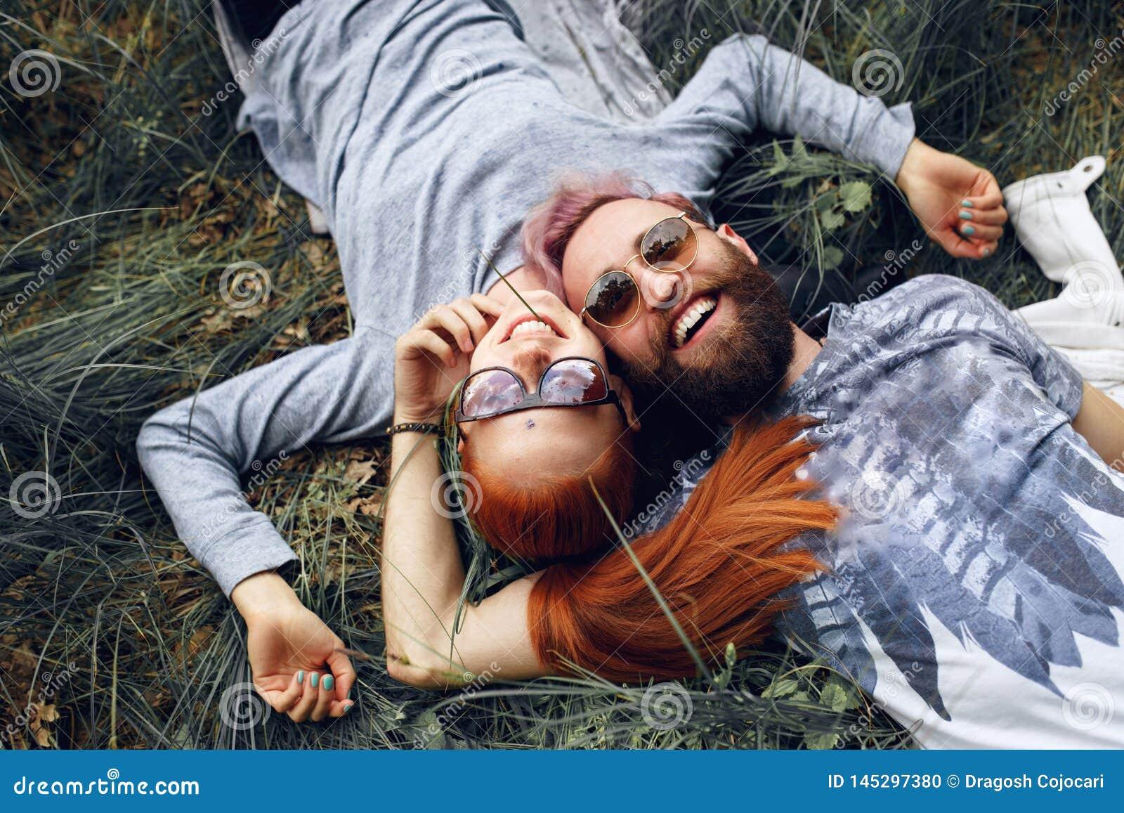 幸福行家夫妇,在太阳镜,红发妇女和有胡子的人,安装下来在绿草