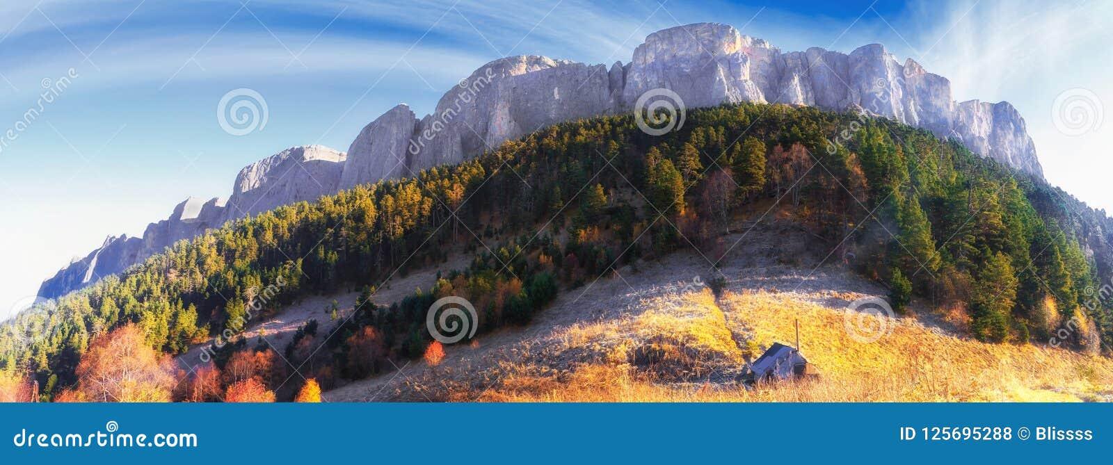 庄严Bolshoy Tkhach落矶山脉峰顶美好的风景金黄秋天风景在日出的蓝天下与木游览