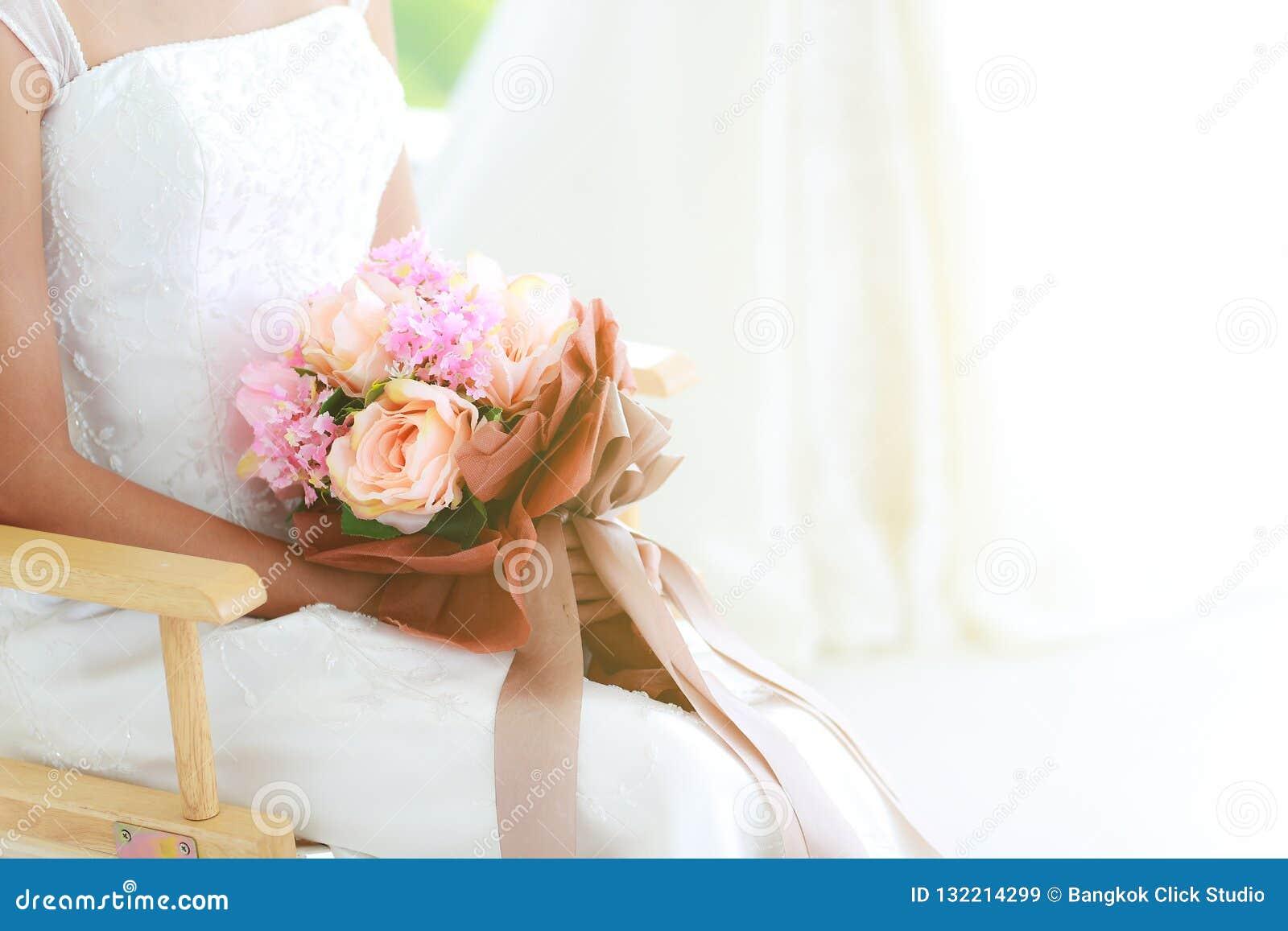 庄稼身体,关闭拿着美丽的花束的新娘坐o