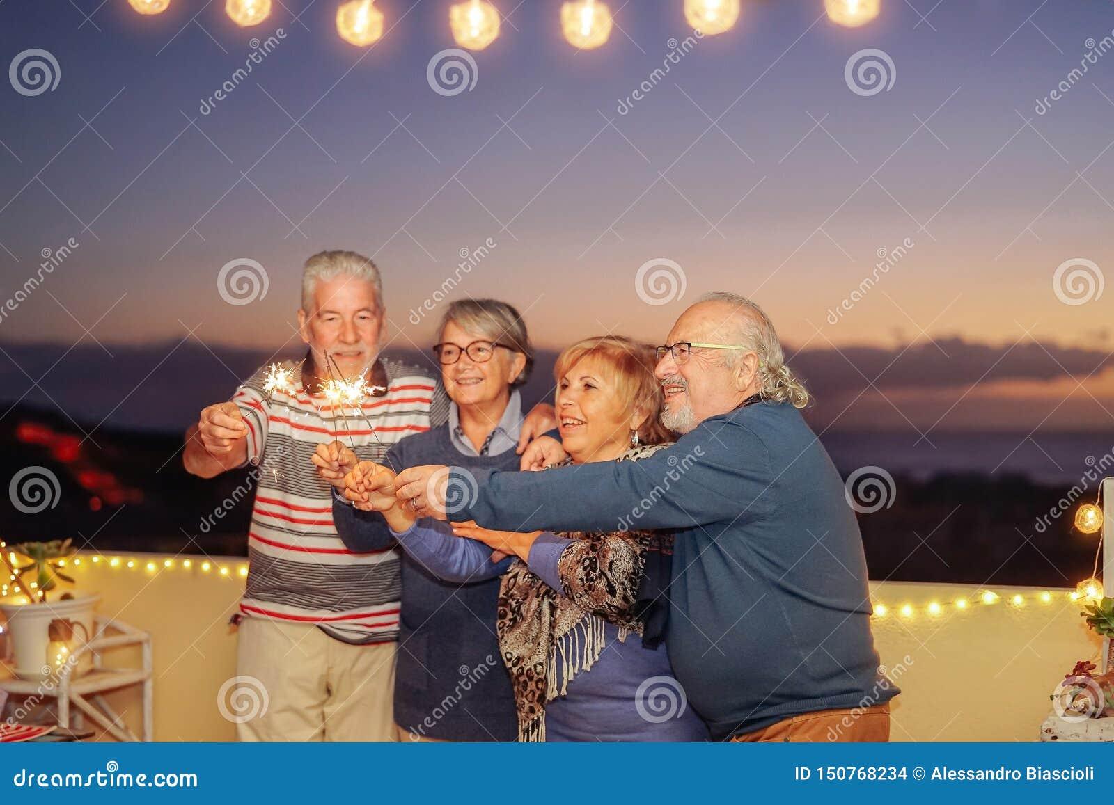 庆祝与闪烁发光物的愉快的资深朋友生日夏夜担任主角室外-老人获得乐趣在大阳台