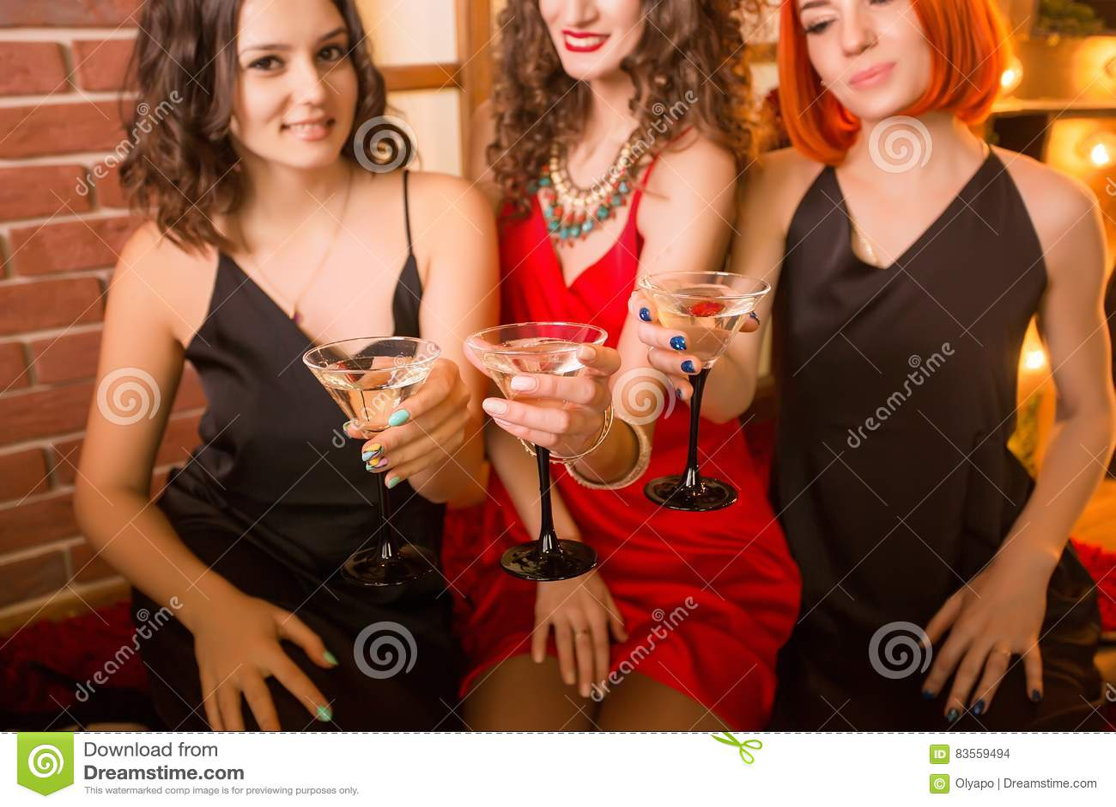 庆祝他们的生日的三个女孩 在相同礼服、黑色和红色的妇女的聚会