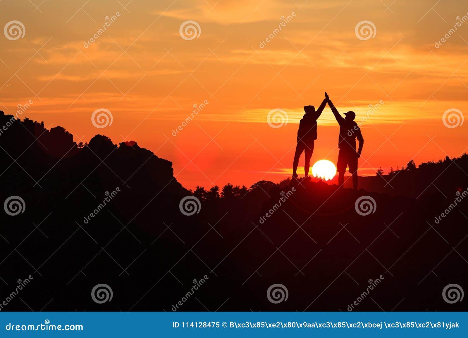 庆祝在富启示性的山日落的配合夫妇
