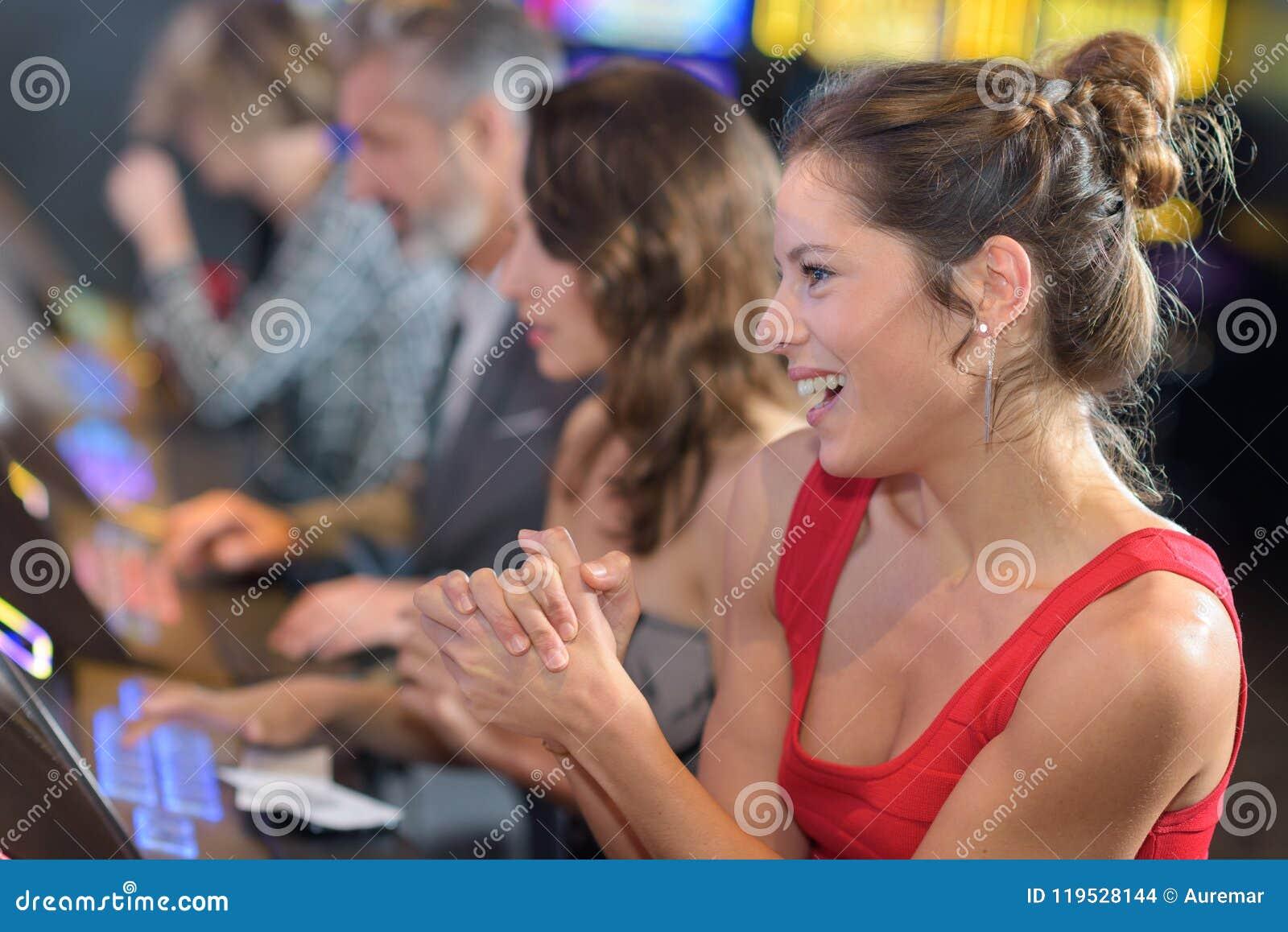 庆祝在老虎机的妇女胜利在赌博娱乐场
