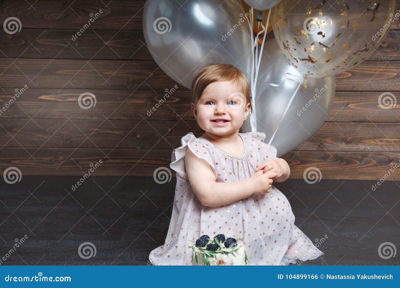 庆祝她的与蛋糕和气球的逗人喜爱的可爱的女婴画象第一个生日