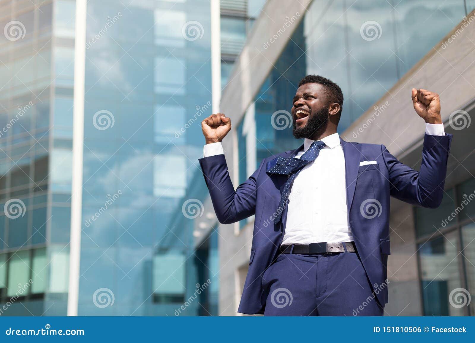 庆祝成功和保留手的激动的年轻商人提高了站立户外 r