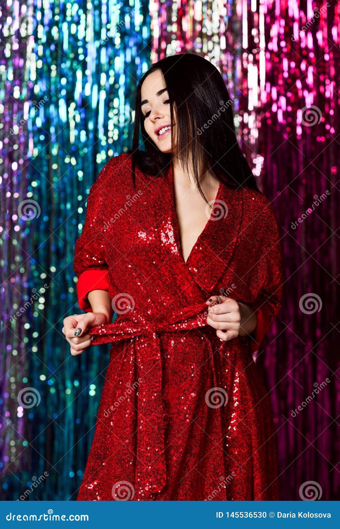 庆祝深色的妇女,获得乐趣在党 一个愉快的微笑的女孩的画象一件时髦的迷人的发光的红色礼服的
