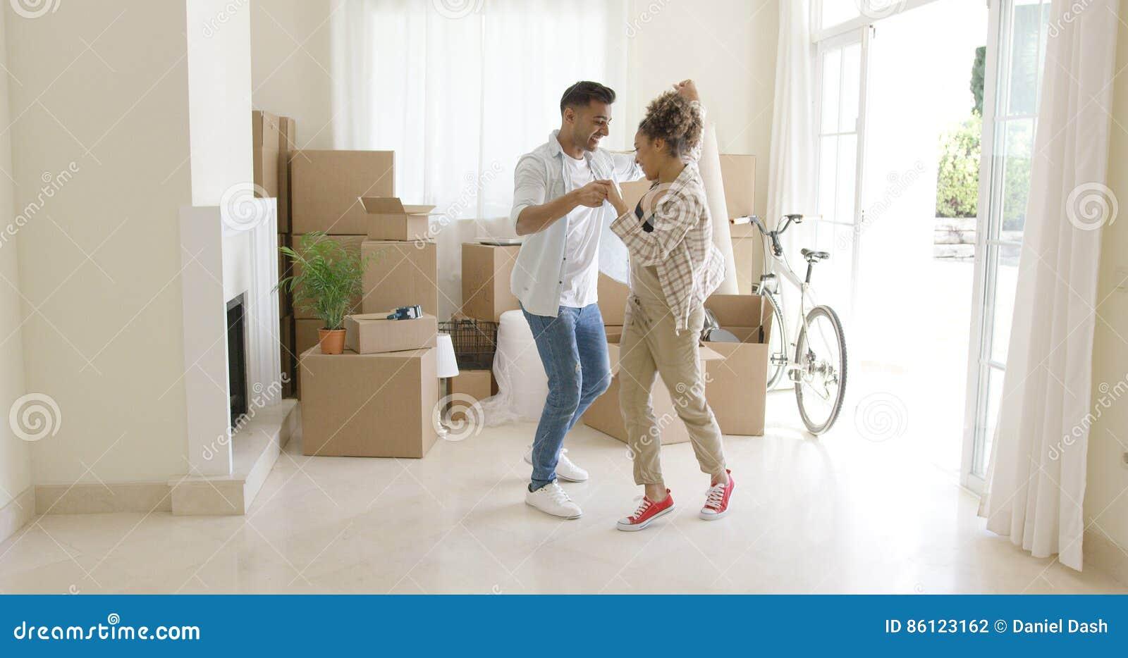 庆祝移动的家的愉快的年轻夫妇