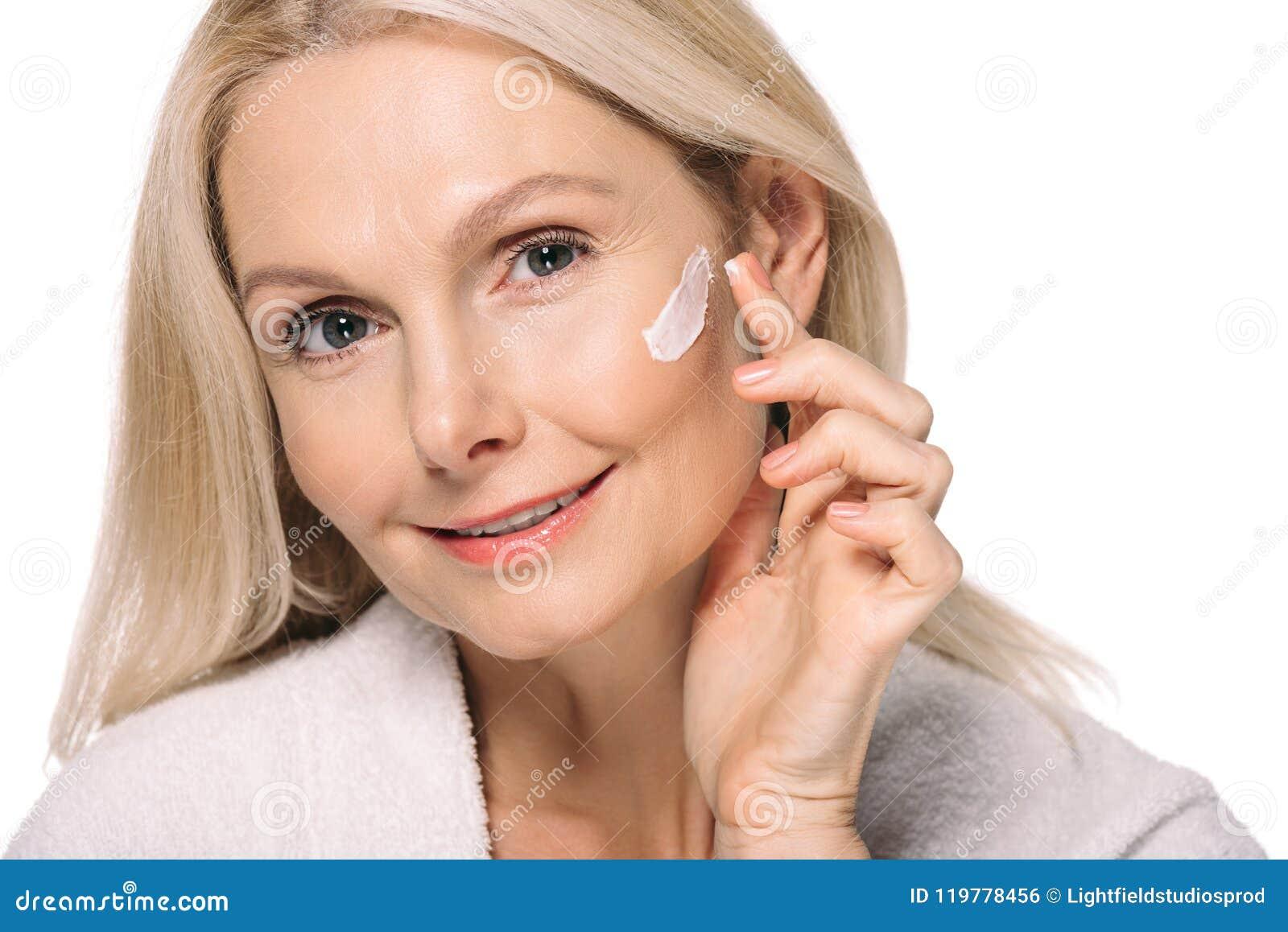 应用化妆奶油的微笑的成熟妇女