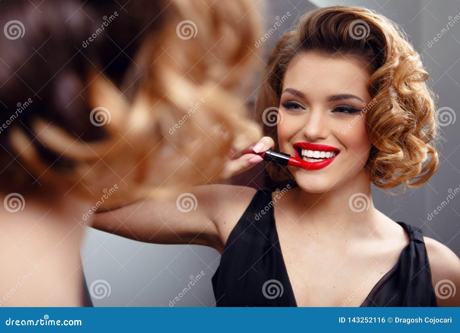 应用在嘴唇的诱人的性感的年轻女人红色口红,看在镜子 减速火箭的概念 使用化妆用品