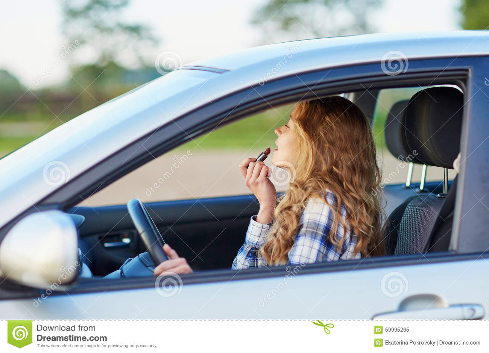 应用在汽车的妇女唇膏,当驾驶时