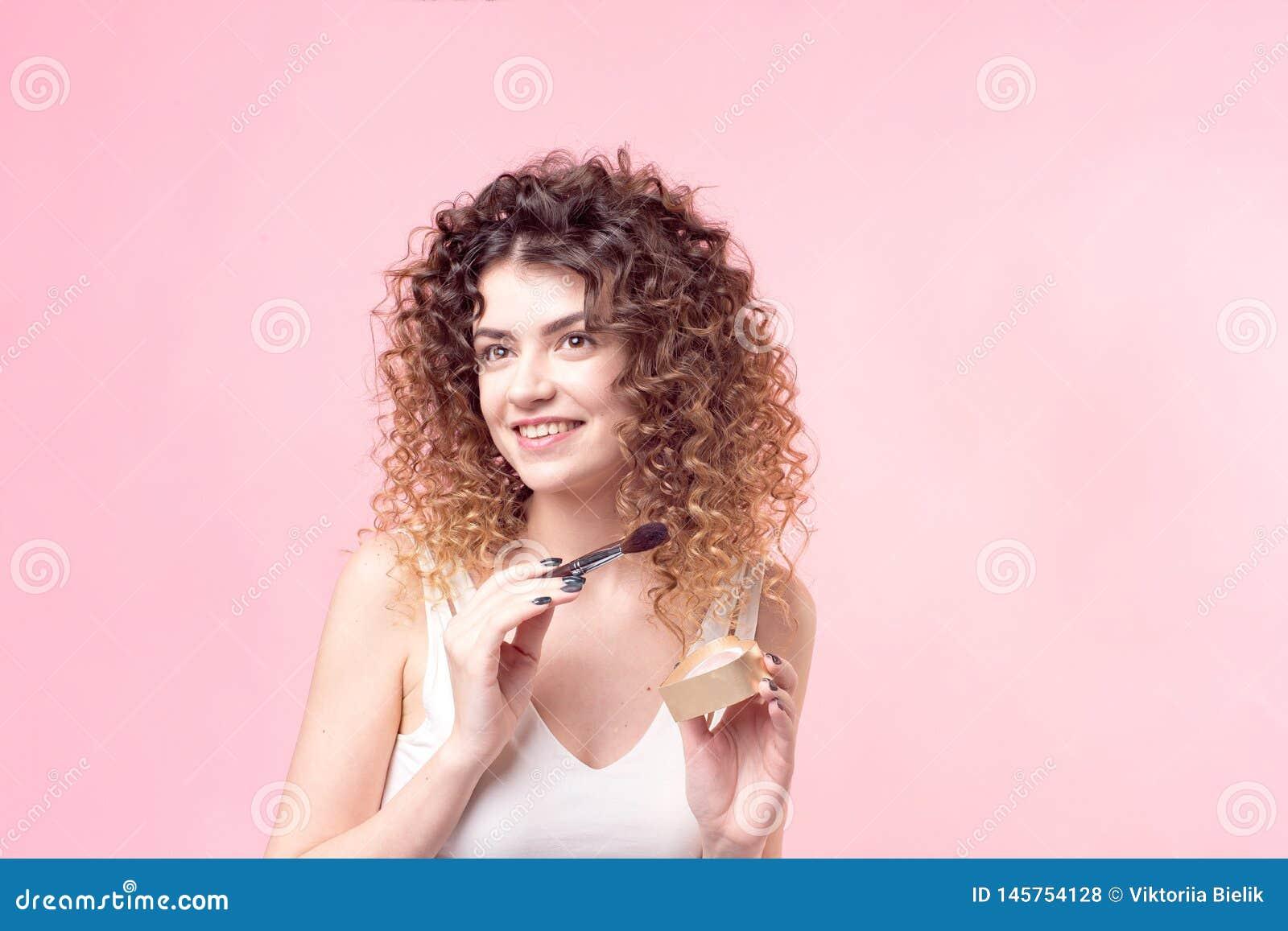 应用基础粉末的美丽的年轻女人或脸红与构成刷子