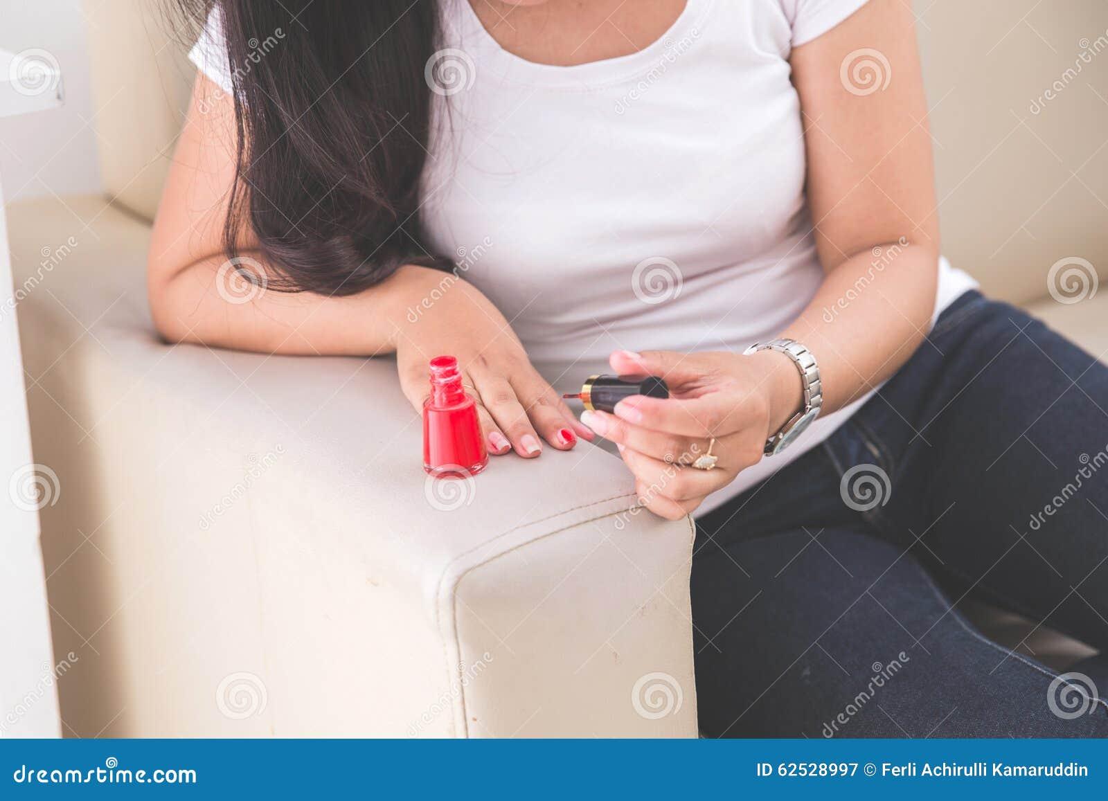 应用指甲油的妇女入她的钉子
