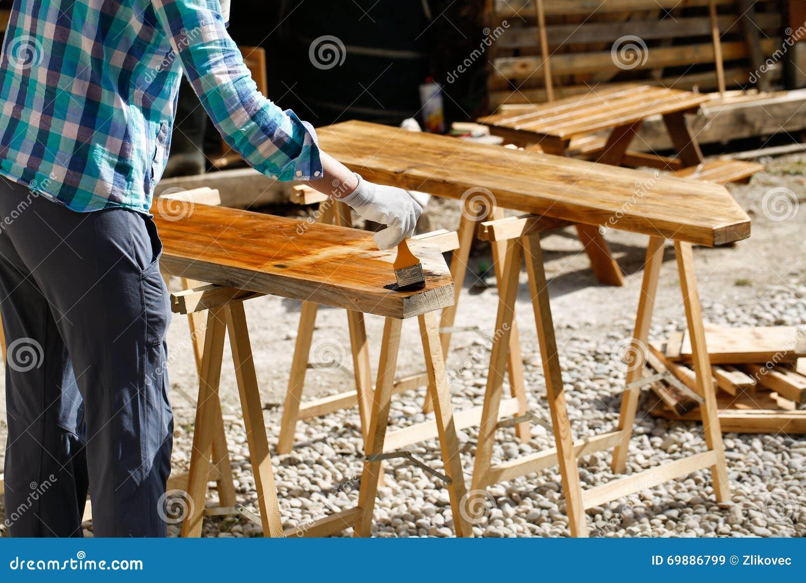 应用新鲜的木治疗油漆的工作者
