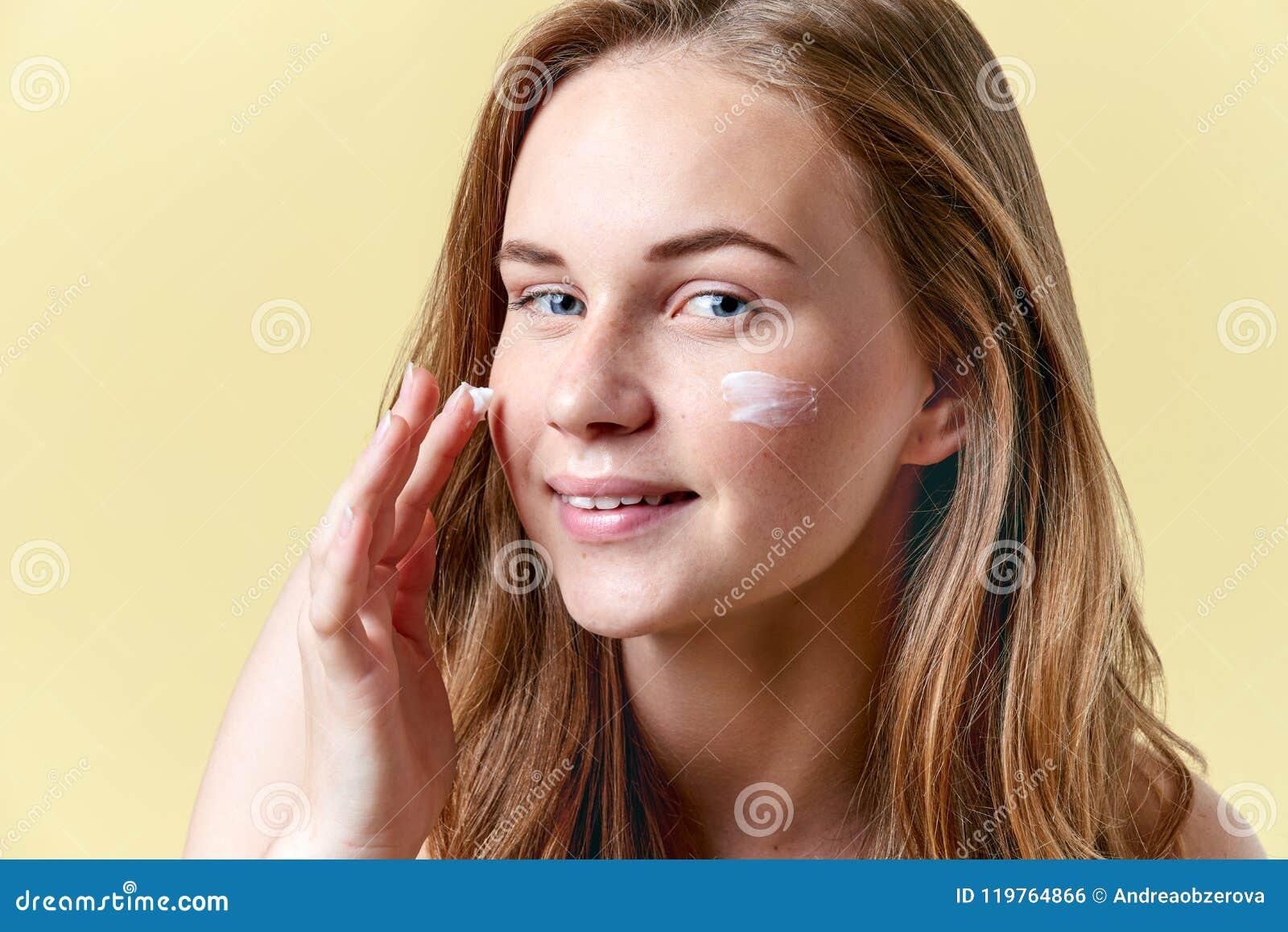 应用润肤霜面霜,微笑和看照相机的年轻可爱的红头发人妇女 秀丽, skincare