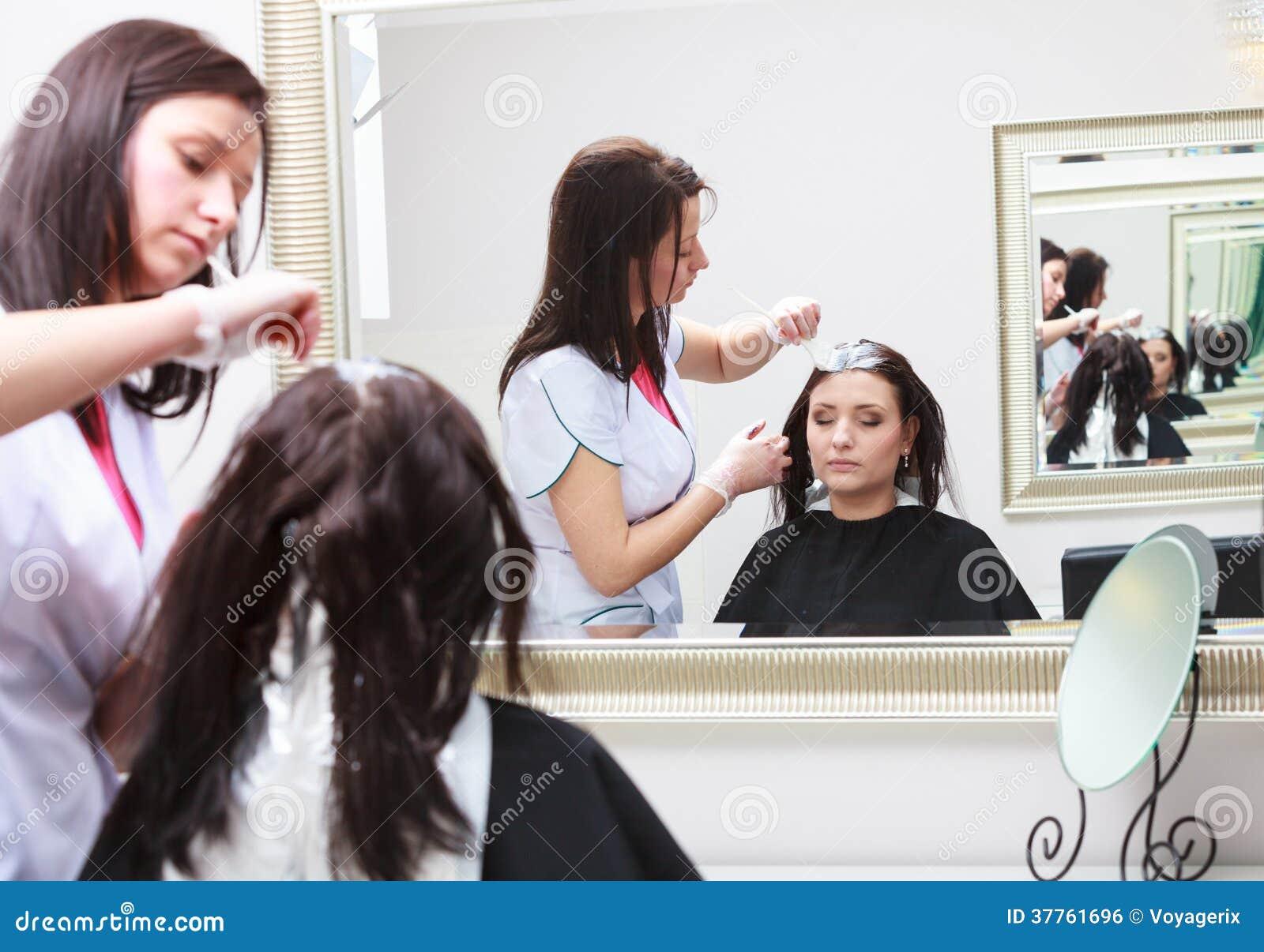 应用颜色女性顾客的美发师在沙龙,做染发剂图片