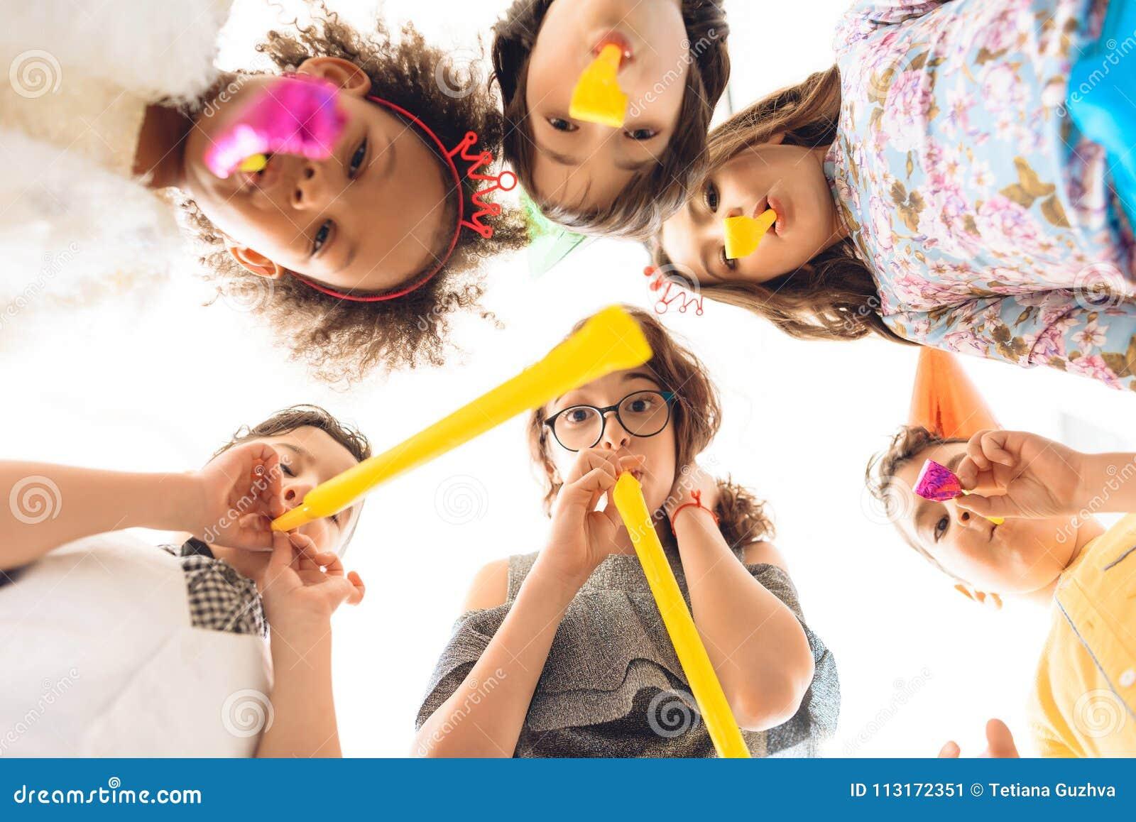 底视图 快乐的孩子在欢乐管子吹在生日聚会