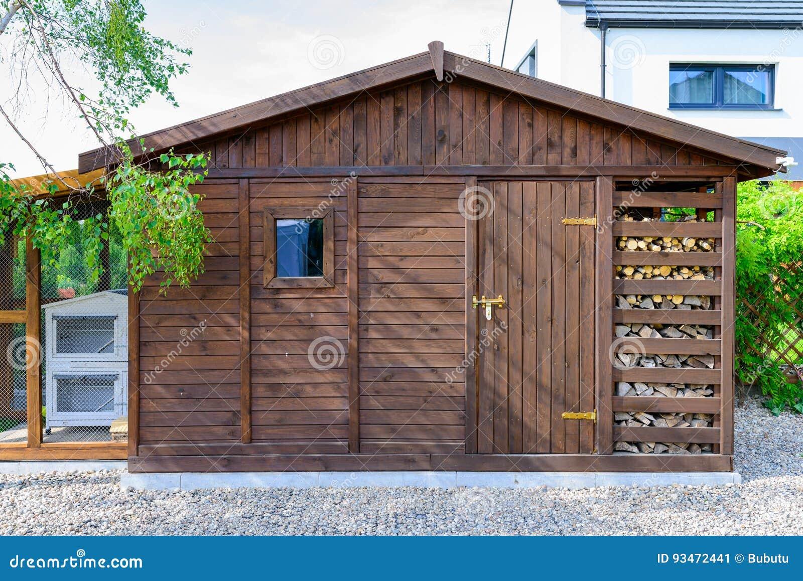 庭院在春天流洒了外部,有堆木材的棚的