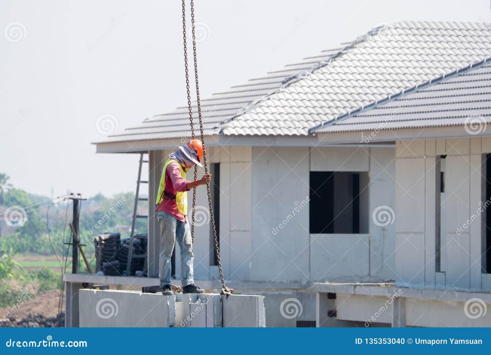 建筑工人安装起重机勾子在预制混凝土墙壁,预铸的房子