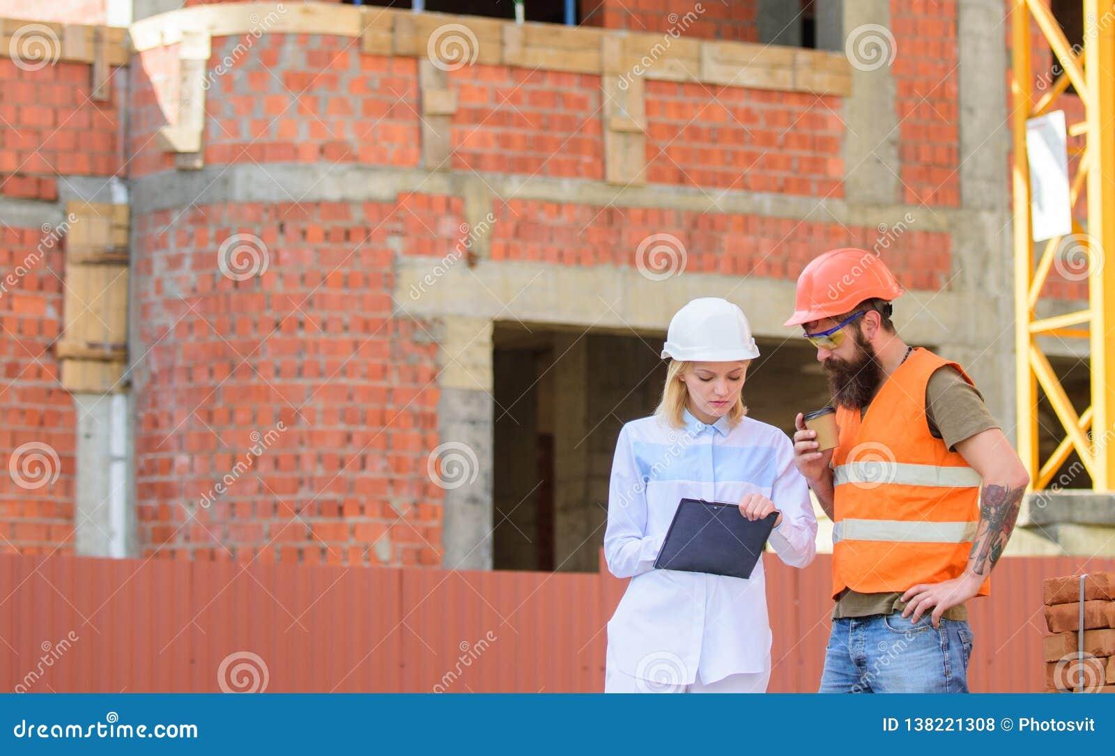 建筑队通信概念 妇女工程师和建造者传达工地工作 谈论进展计划