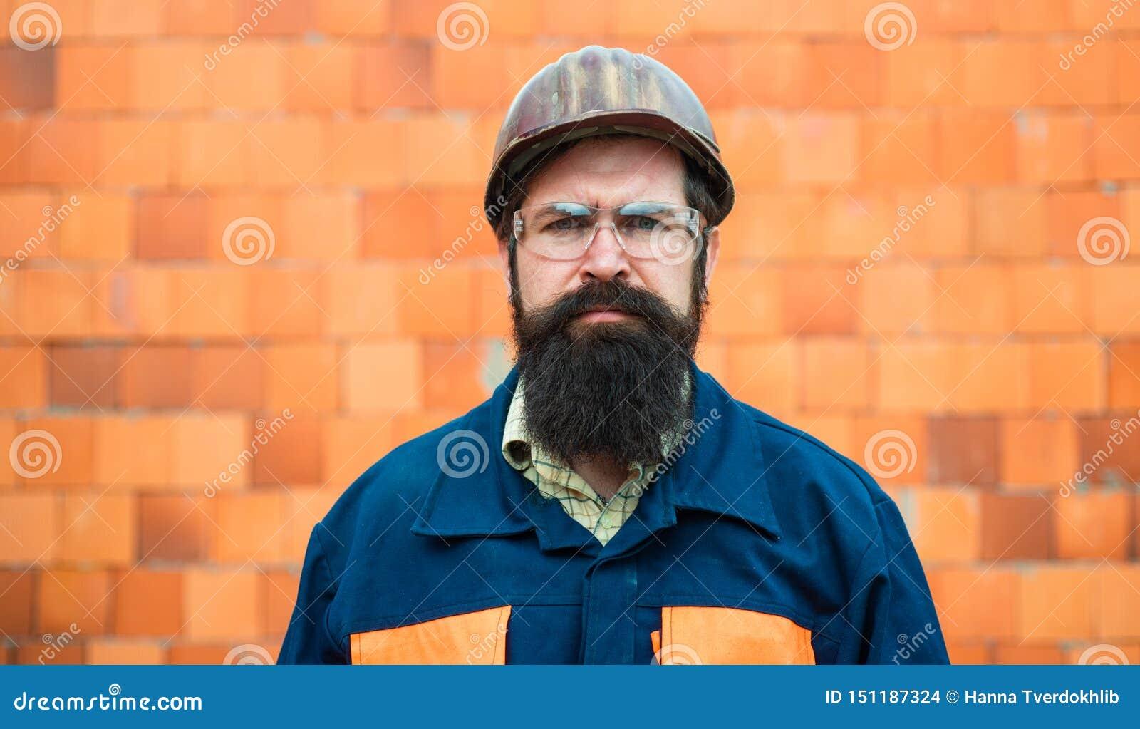 建造者 画象机械工作者 衣服的有胡子的人与建筑盔甲 英俊的工程师画象