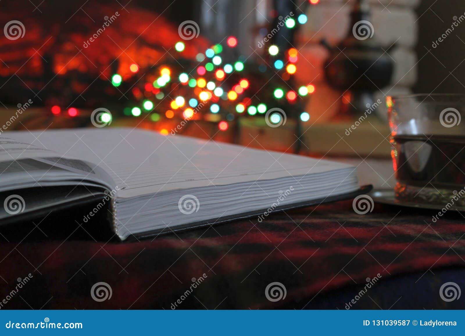 开放日志,透明茶在钢杯座的在一本灼烧的壁炉和圣诞节诗歌选的背景
