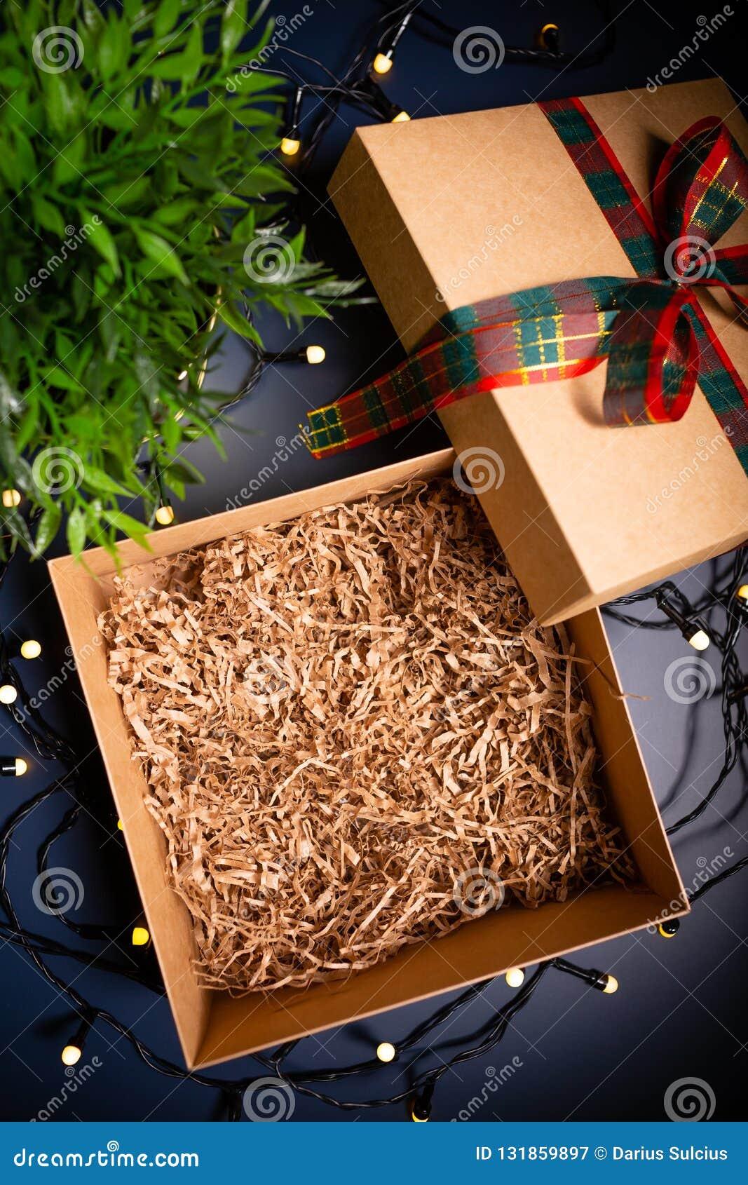 开放有丝带的纸盒当前箱子在装饰光围拢的蓝色背景