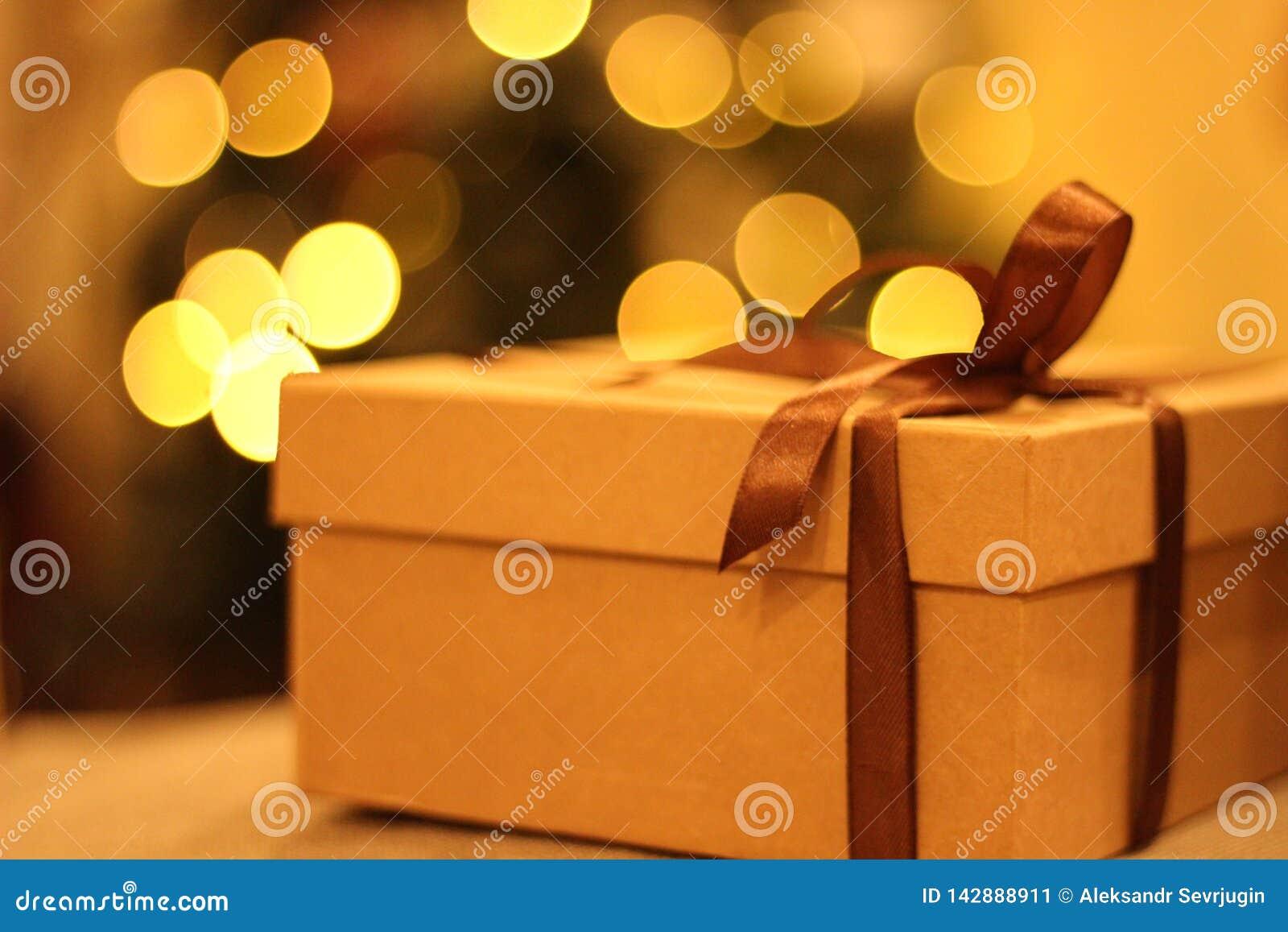 开放的特写镜头和有棕色丝带的闭合的礼物盒