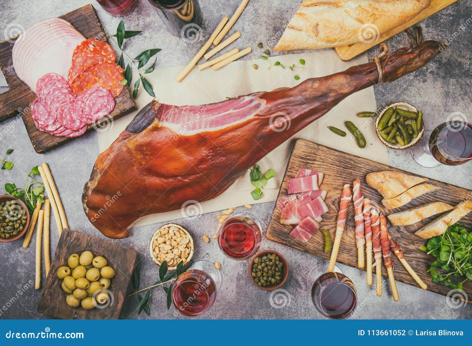 开胃菜制表与西班牙利比亚整个火腿jamon serrano、快餐、橄榄和红色和玫瑰酒红色 Flate位置 顶视图
