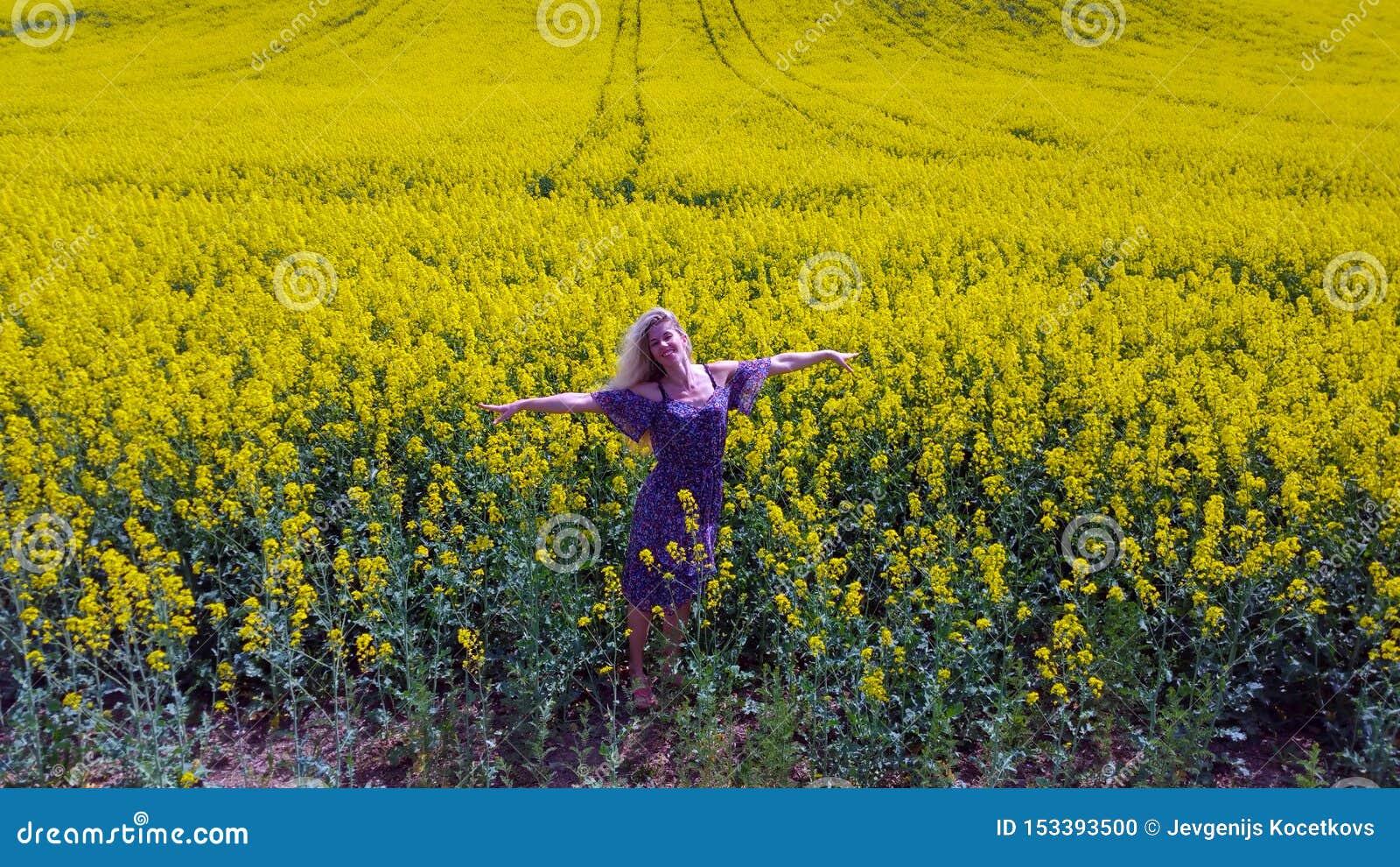 开花的黄色油菜籽领域的愉快的白肤金发的女孩