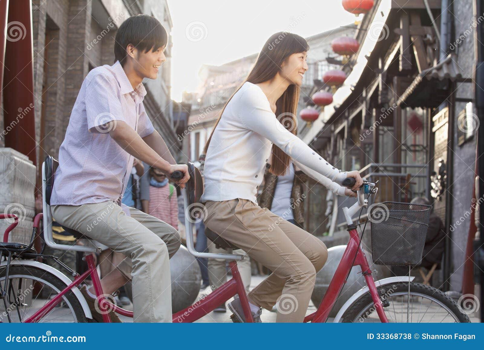 年轻异性爱夫妇侧视图在一辆纵排自行车的在北京