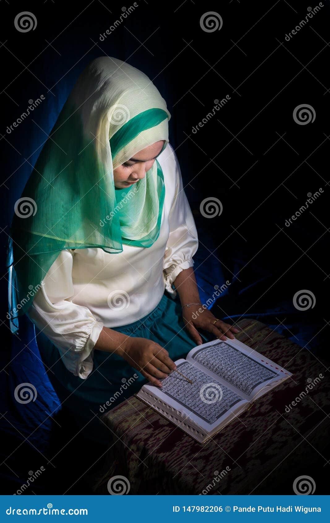 弗洛勒斯,INDONESIA-JUNE 25 2014年:一个十几岁的女孩大约佩带hijab的15-20岁在与种族的一张桌读古兰经