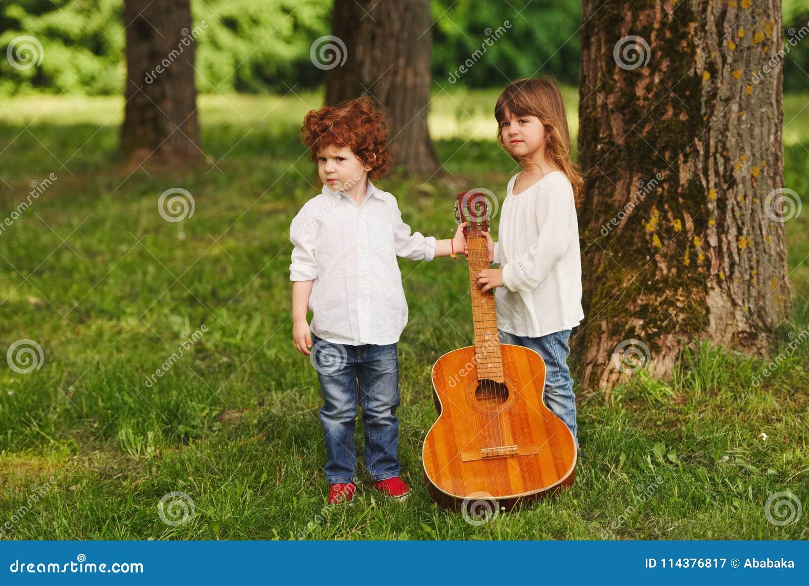 弹吉他的男孩和女孩在夏天公园