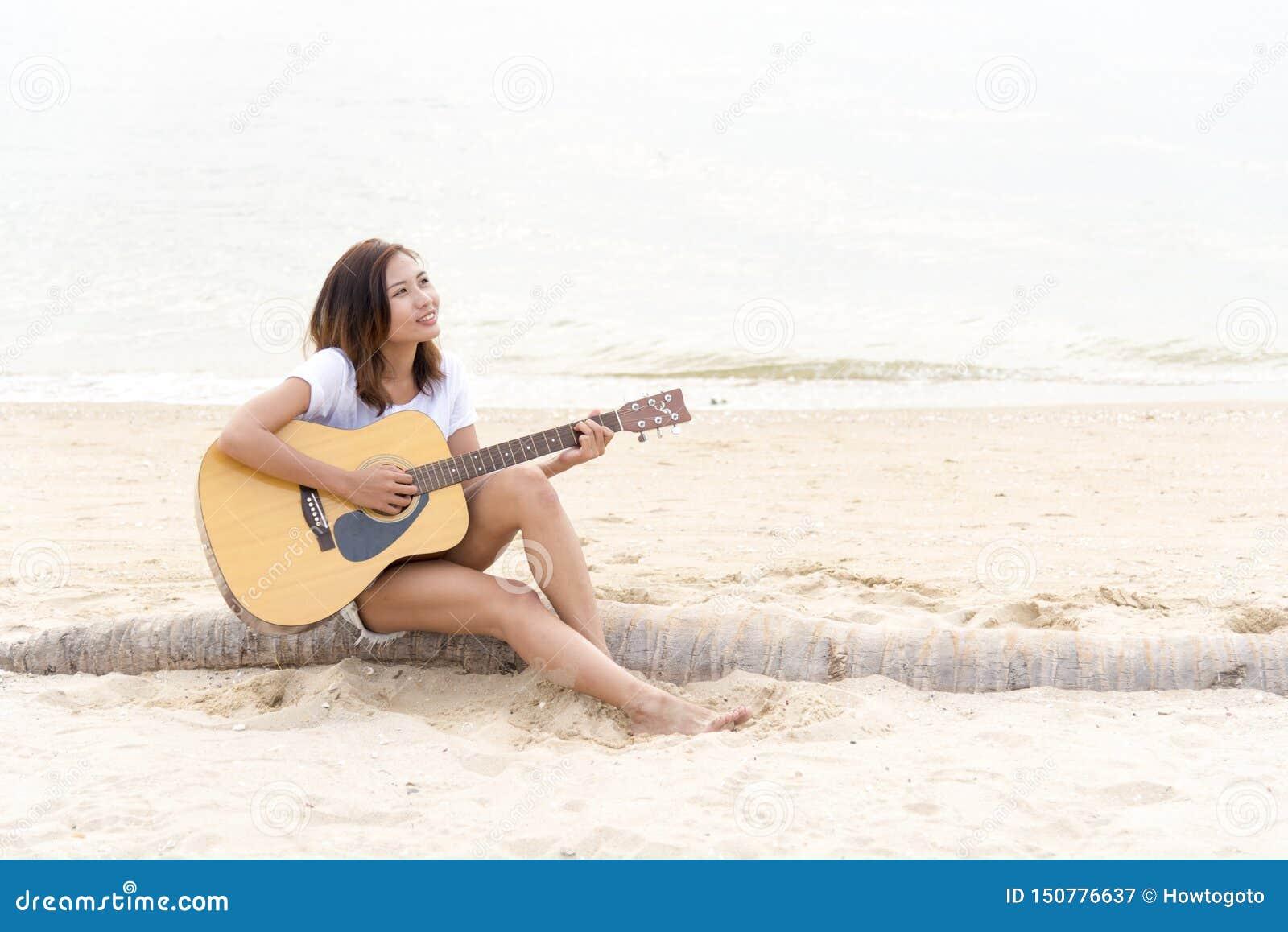 弹在海滩的妇女手吉他 弹经典吉他的音响音乐家 E