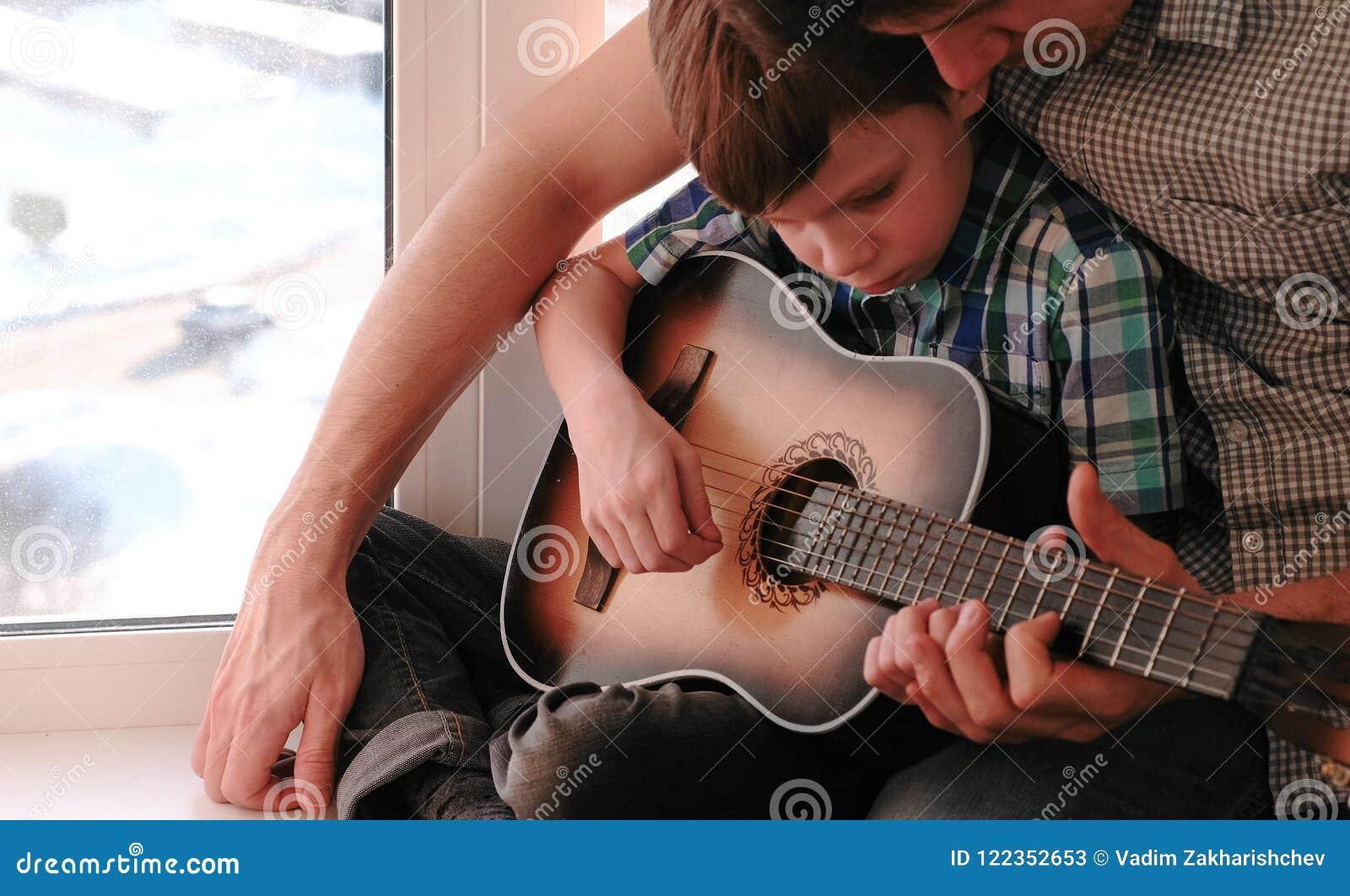 弹奏一个乐器 爸爸教他的儿子弹吉他,坐窗台