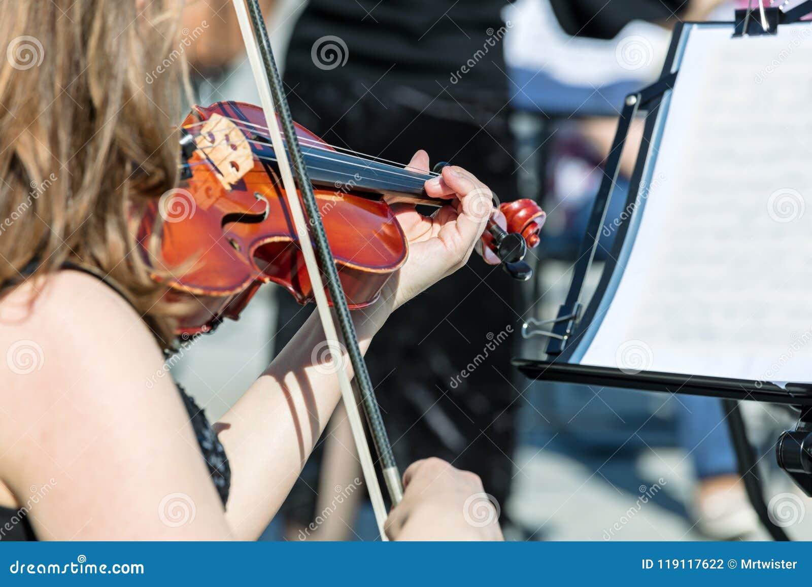 弹小提琴的妇女在古典音乐音乐会期间