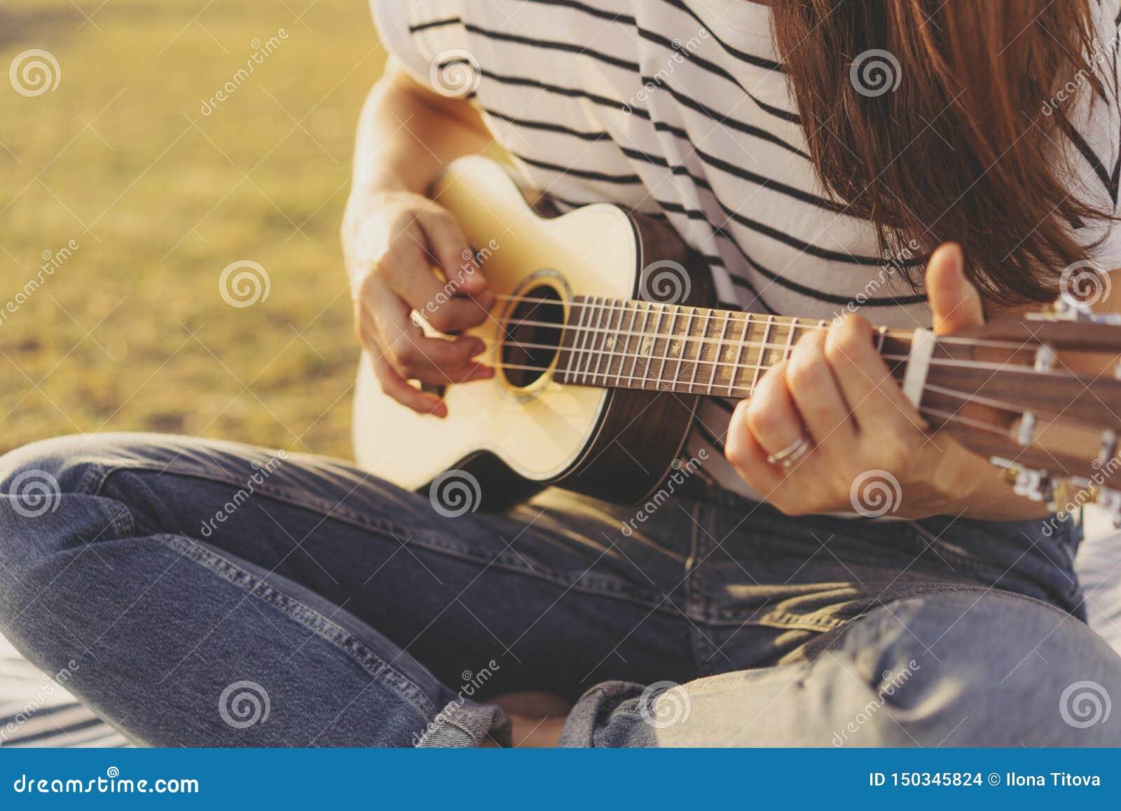 弹尤克里里琴吉他的女性手特写镜头