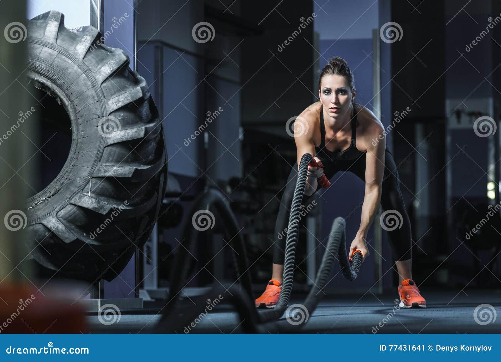 强有力的可爱的肌肉CrossFit教练员作战与绳索的锻炼