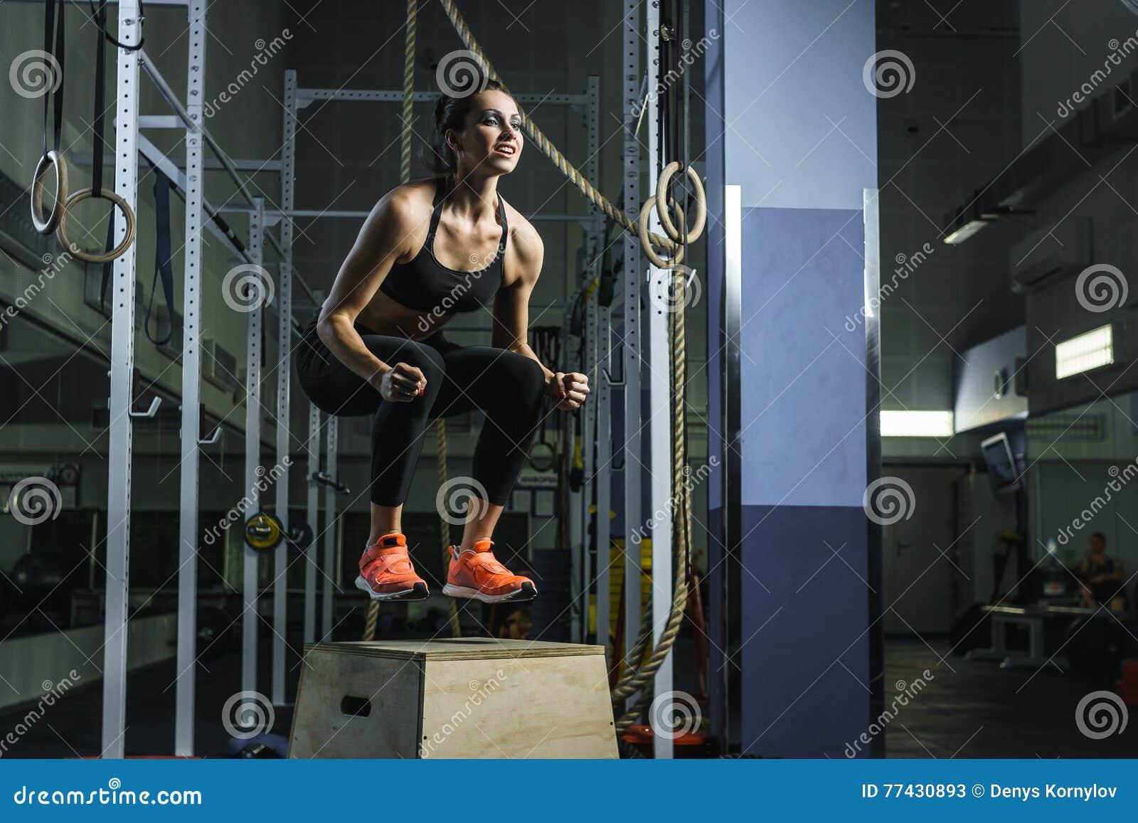 强有力的肌肉妇女CrossFit教练员跳在锻炼期间在健身房