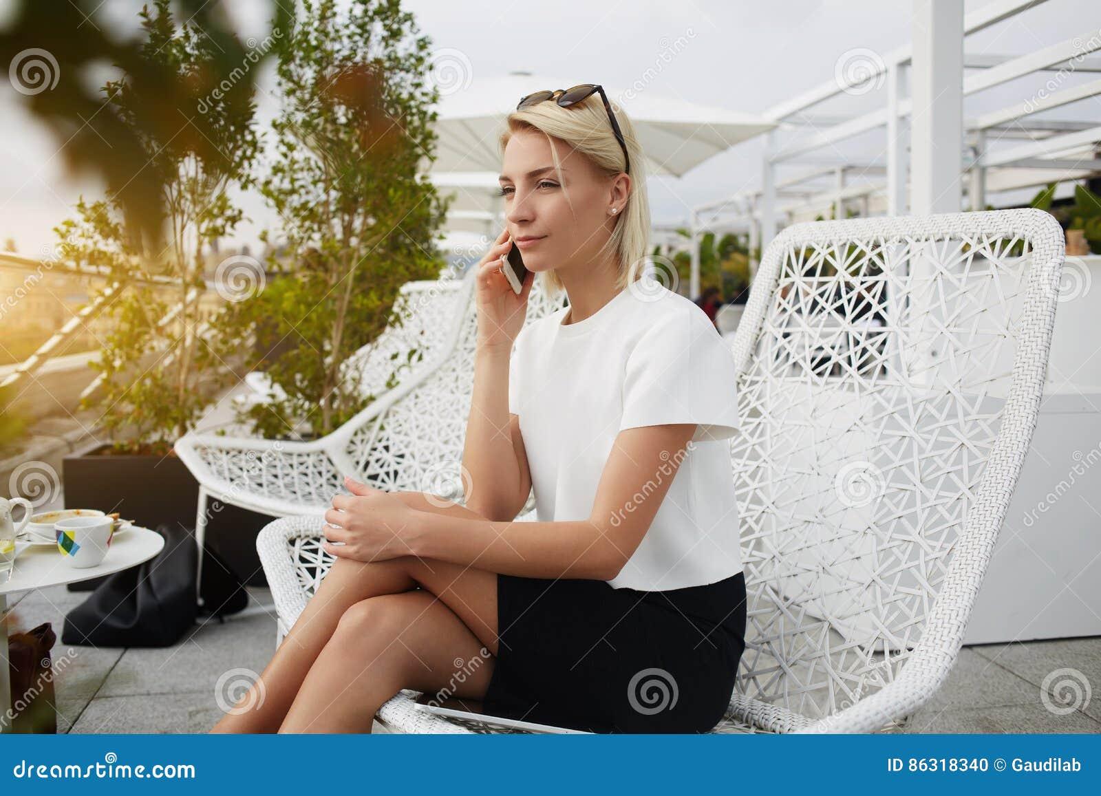 当在咖啡馆时,坐女性熟练的律师通过手机叫