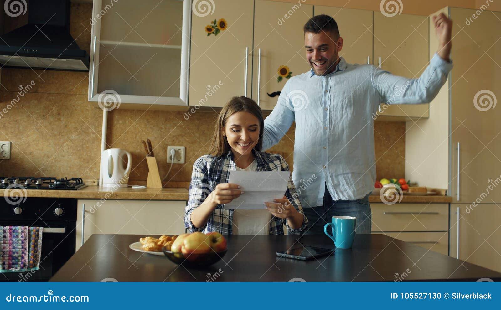 当在家时,食用早餐有吸引力的愉快的夫妇在厨房里收到好消息展开信